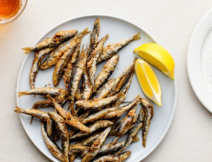 Classic Fried Whitebait (Fried Tiny Fish), fried fish and lemon wedges on a plate