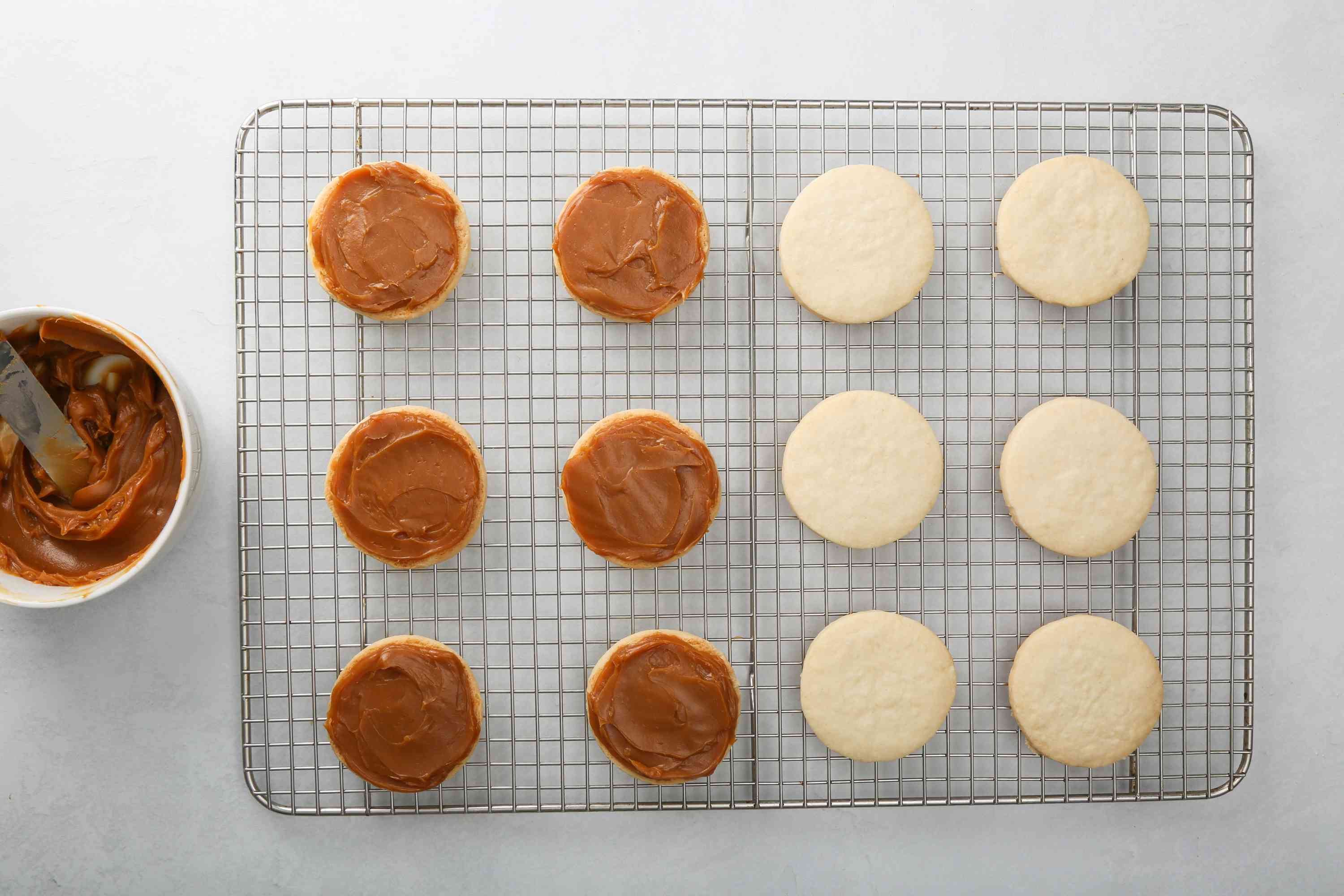 cookies spread with filling on a cooling rack