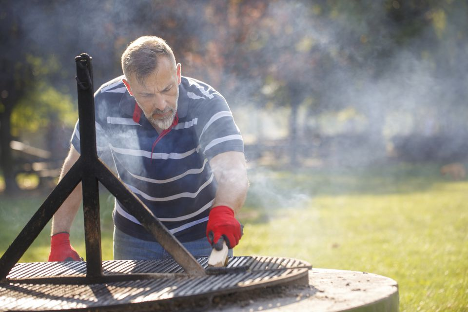 man using grill brush