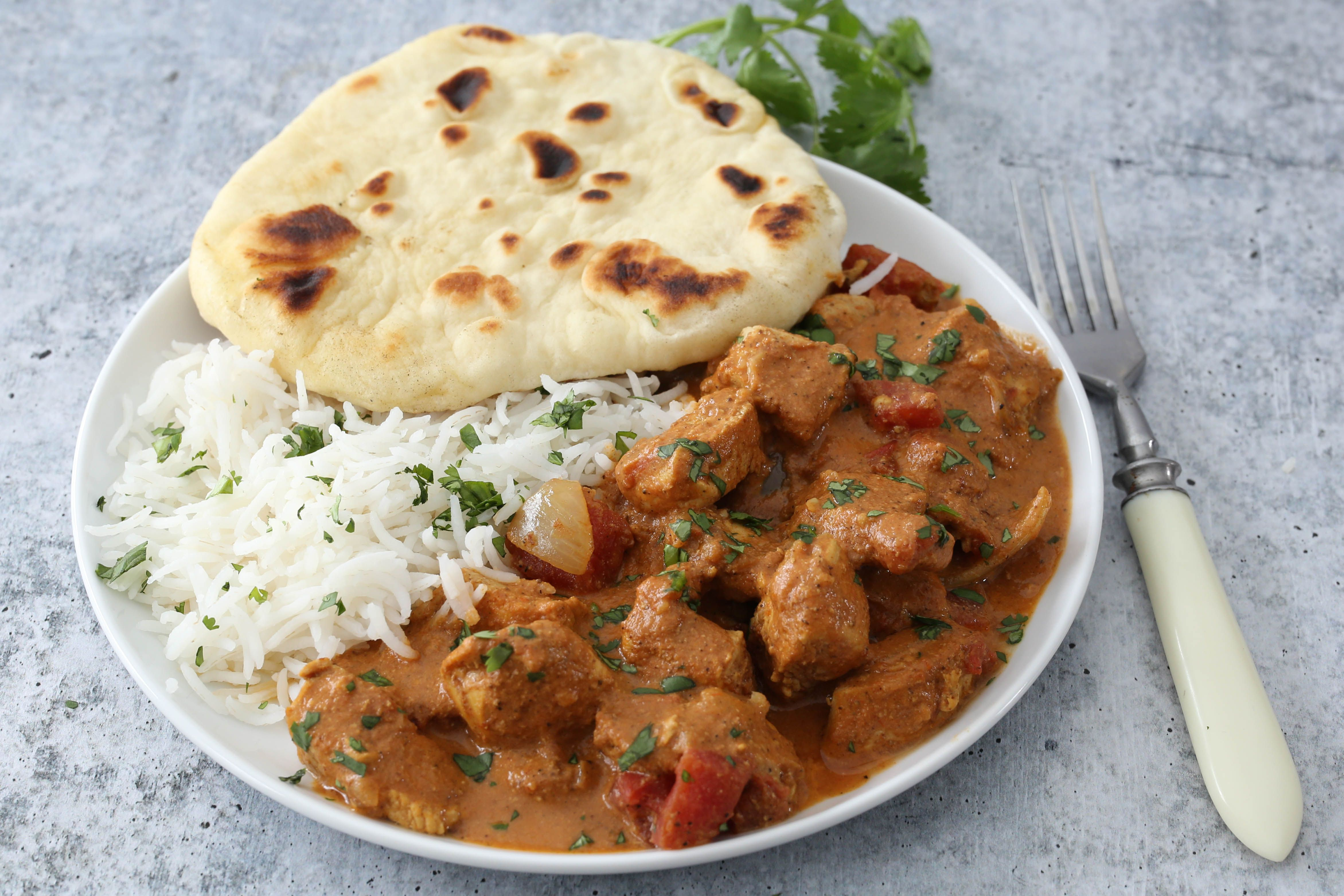 Instant Pot tikka masala with naan bread and rice.