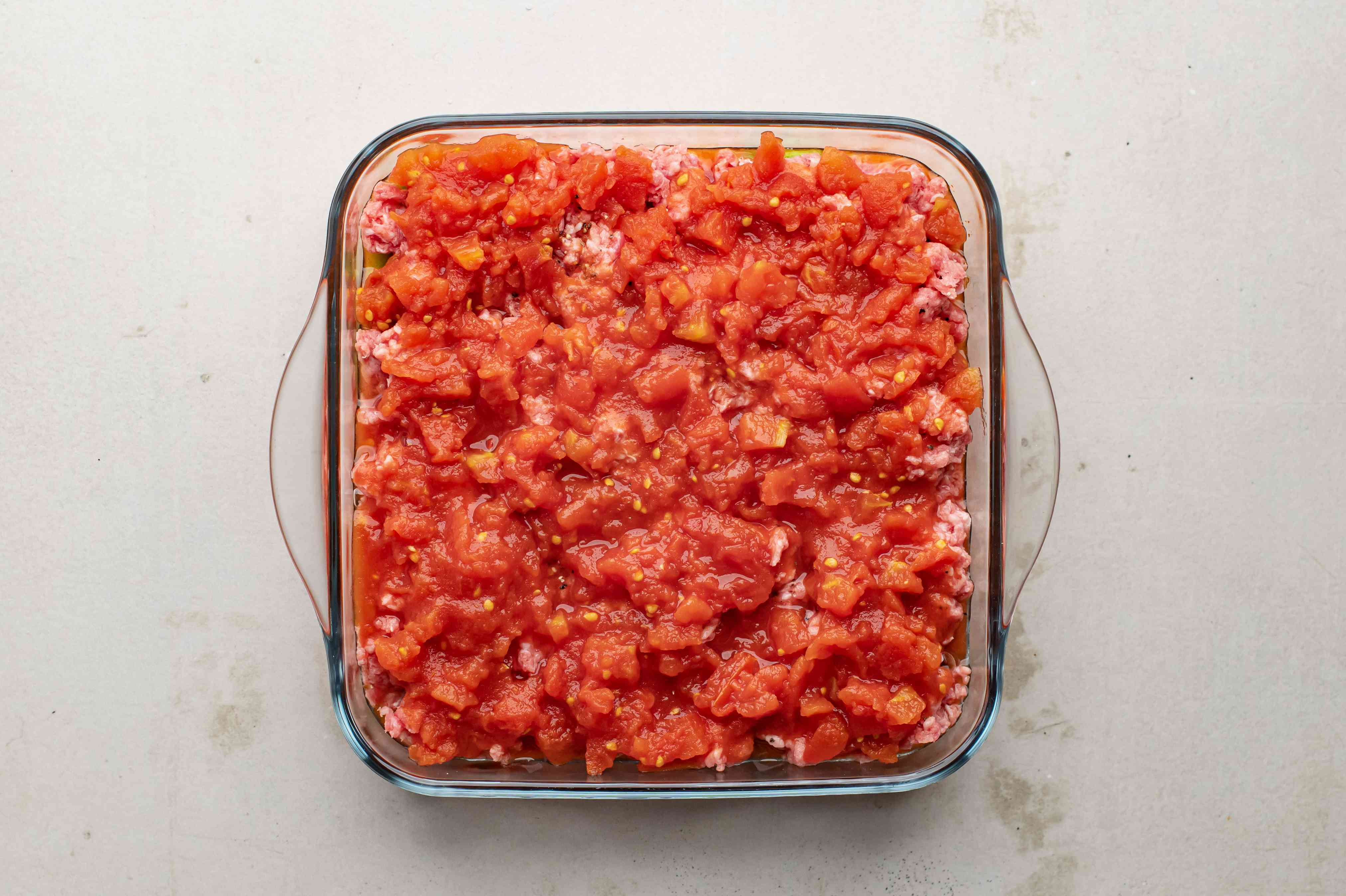 Add can of diced tomatoes to baking dish