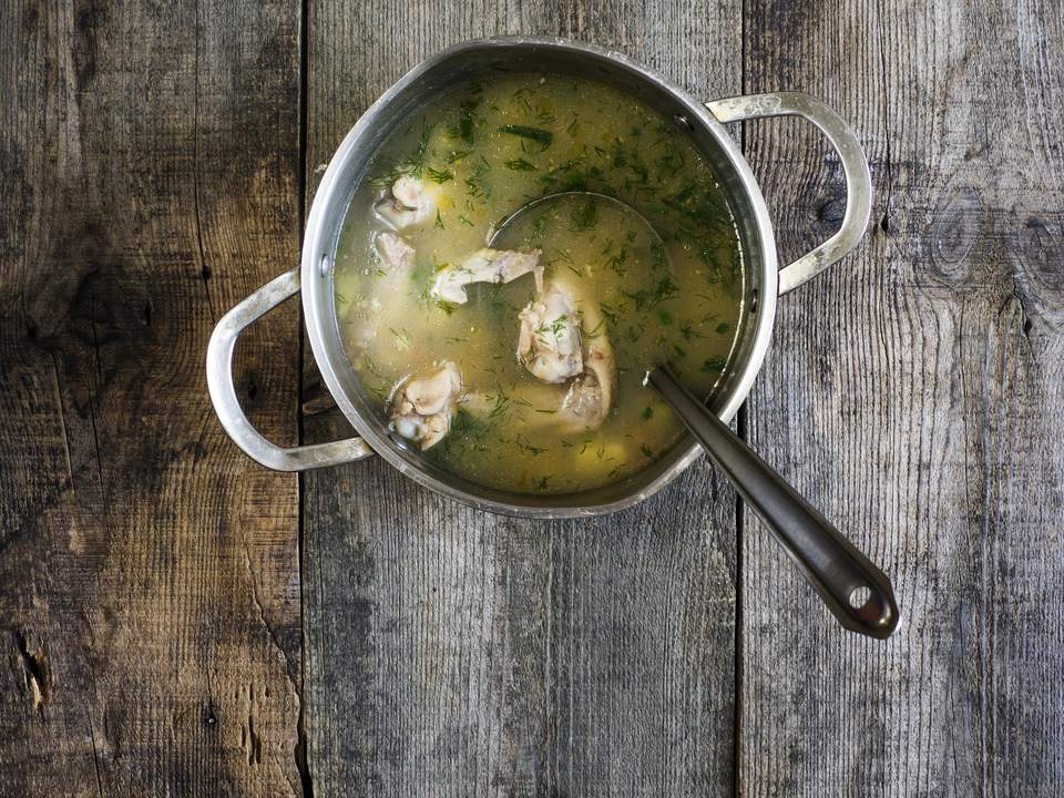 Saucepan of chicken soup on wooden table