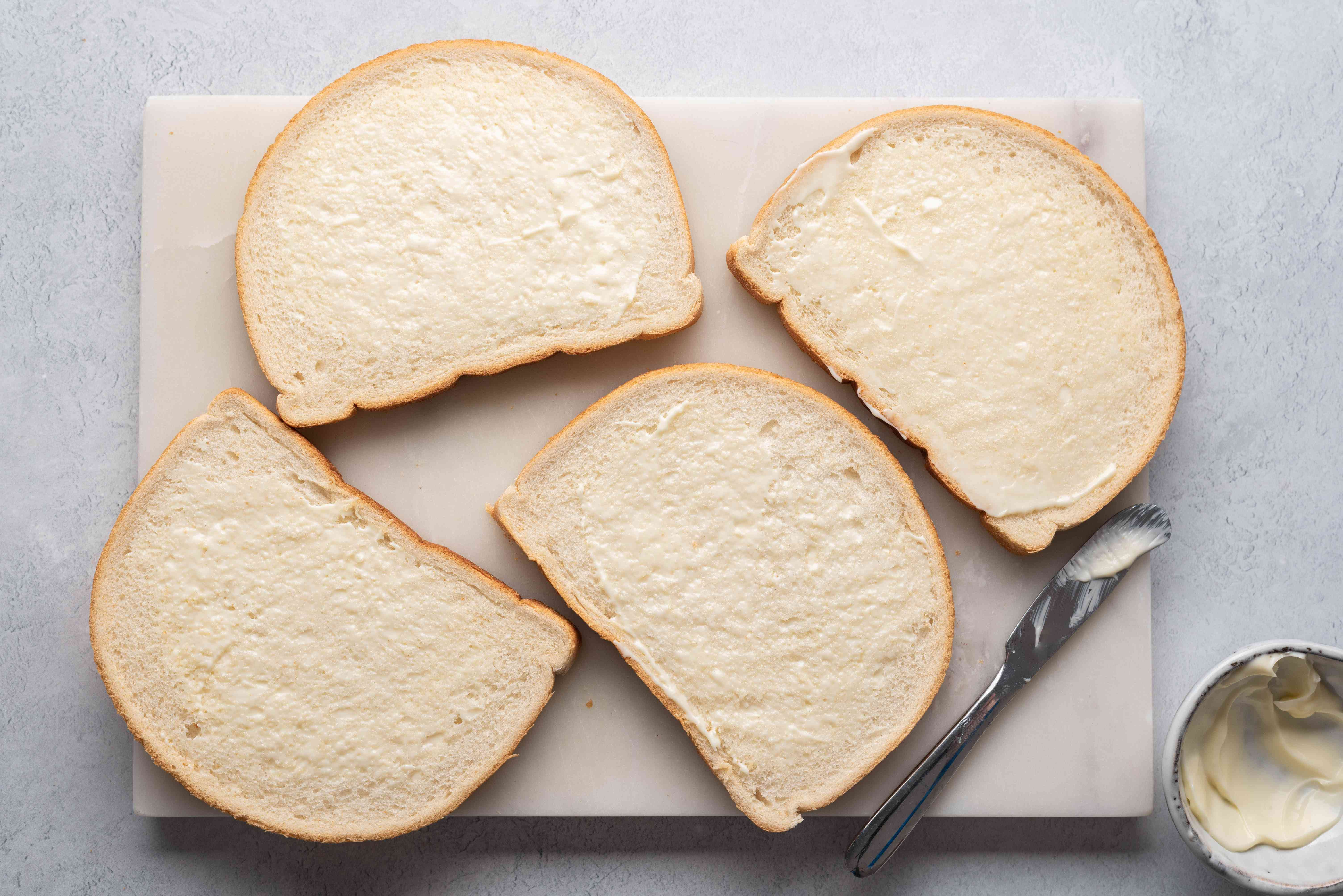 bread slices being spread with mayo