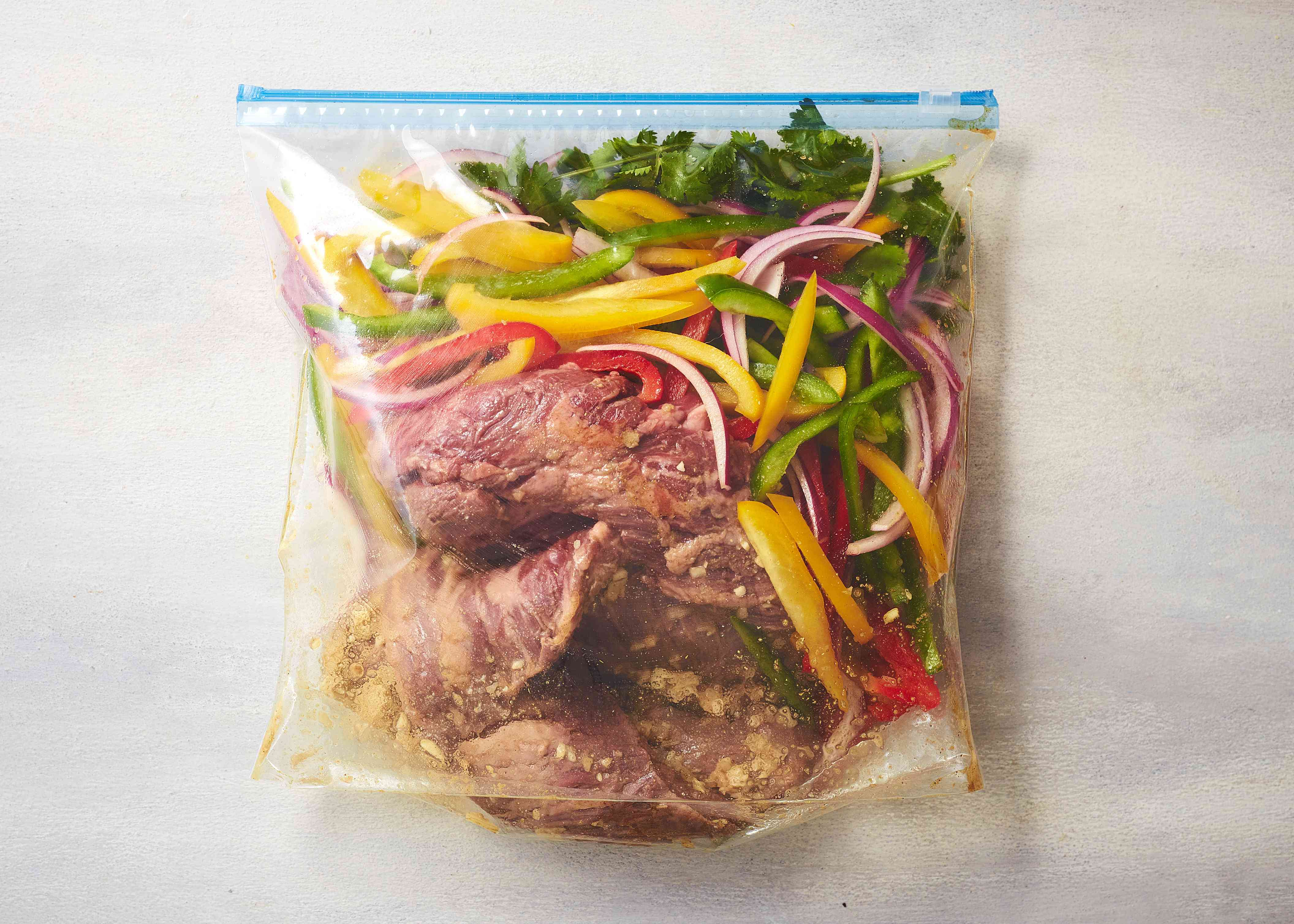 Place the skirt steak, bell peppers, onion, and cilantro sprigs into the bag with the marinade