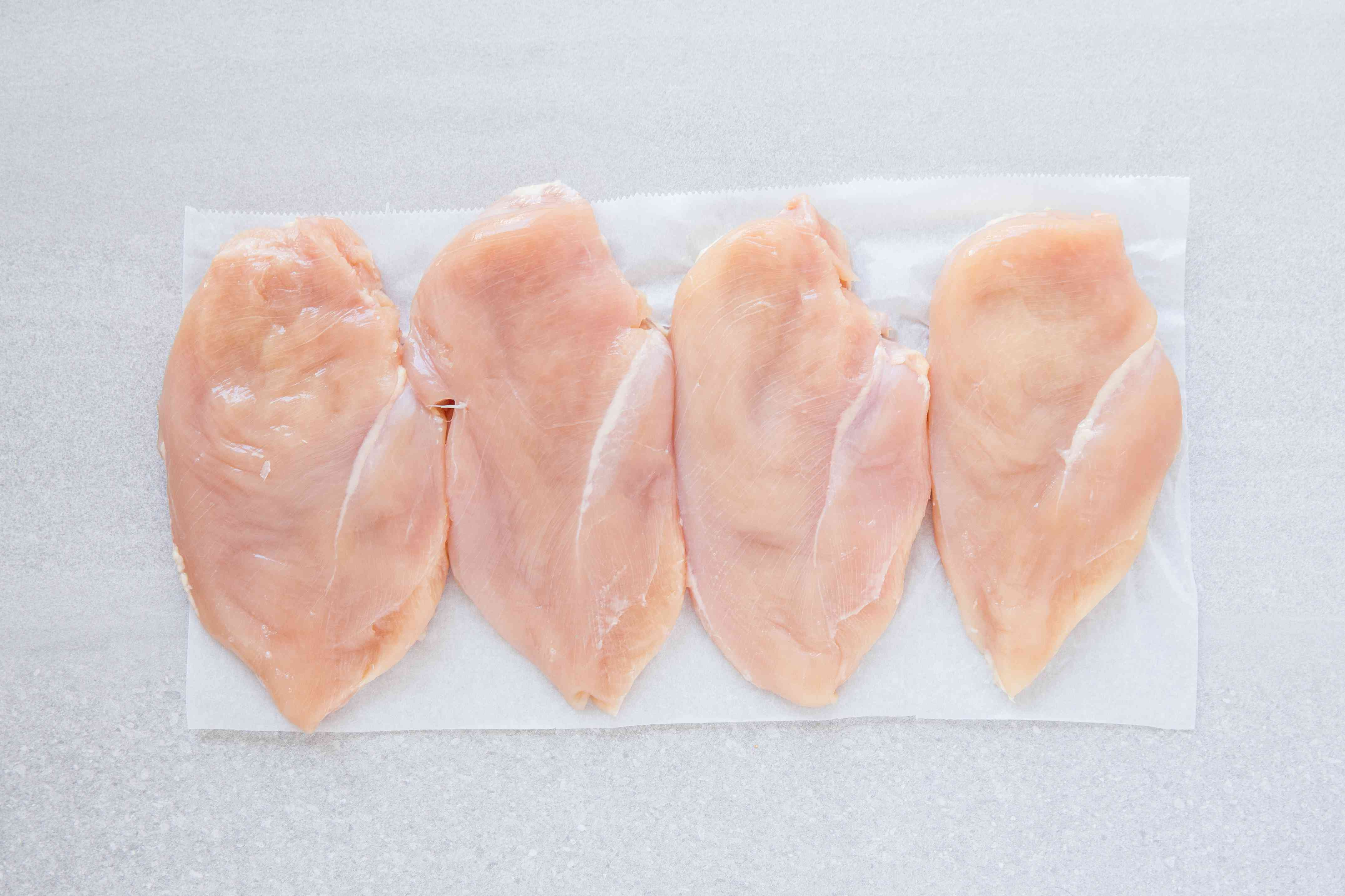 Chicken breasts on waxed paper