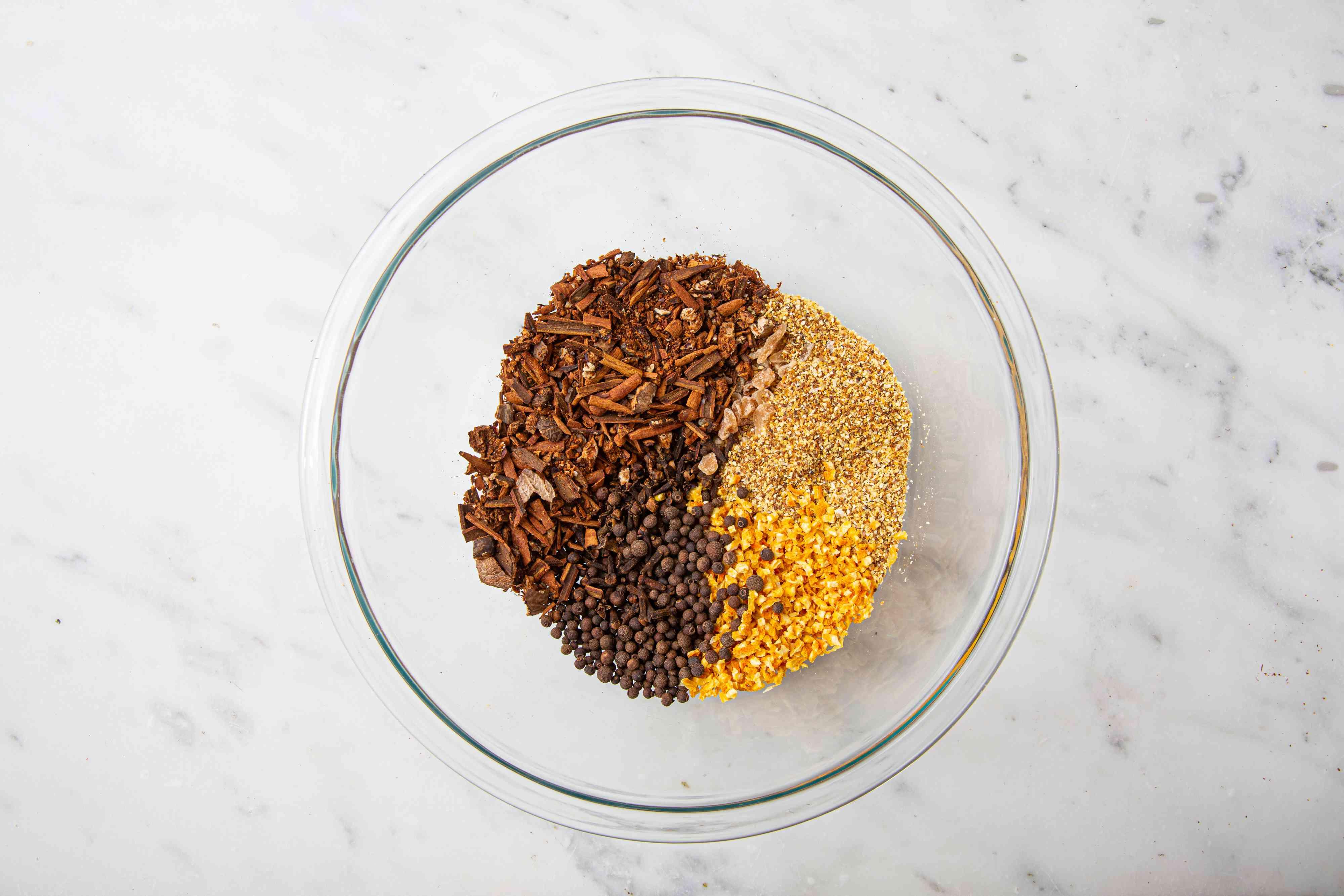orange peel, lemon peel, allspice, cloves, and crystallized ginger in a bowl
