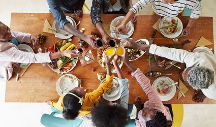Family saying cheers over dinner table