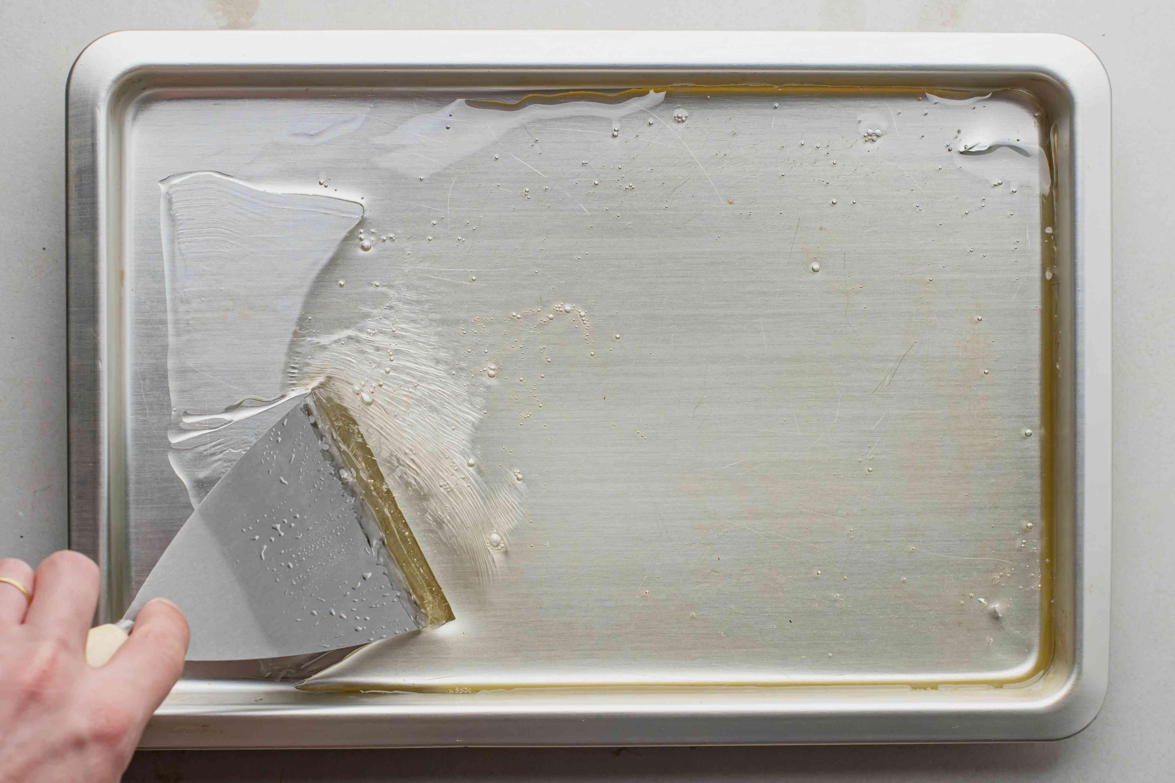 Scraping fondant mixture on a sheet pan