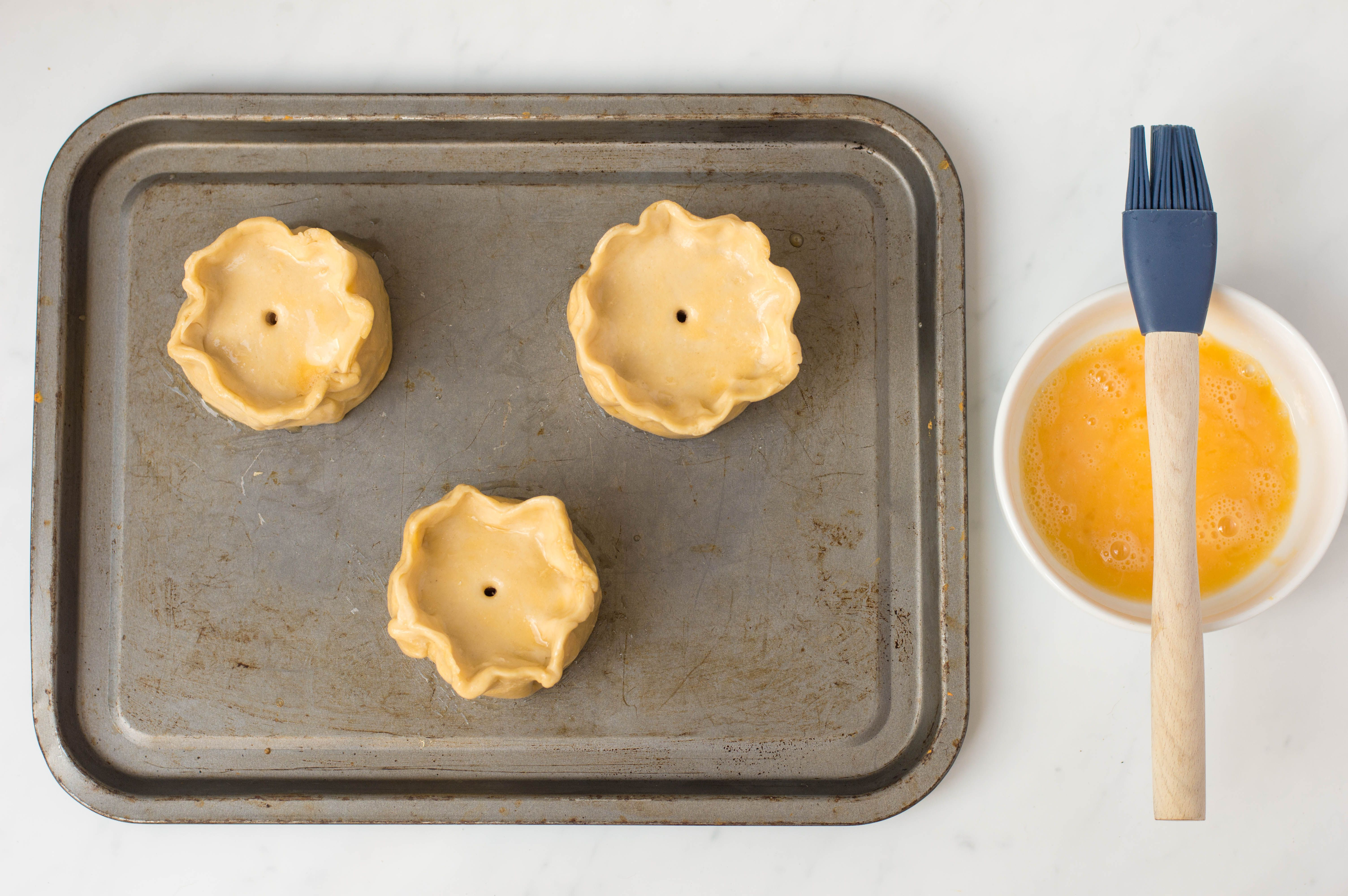 Create egg wash and brush pastry
