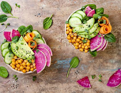 Raw vegan food bowls, with watermelon radish, chickpeas, and cucumbers