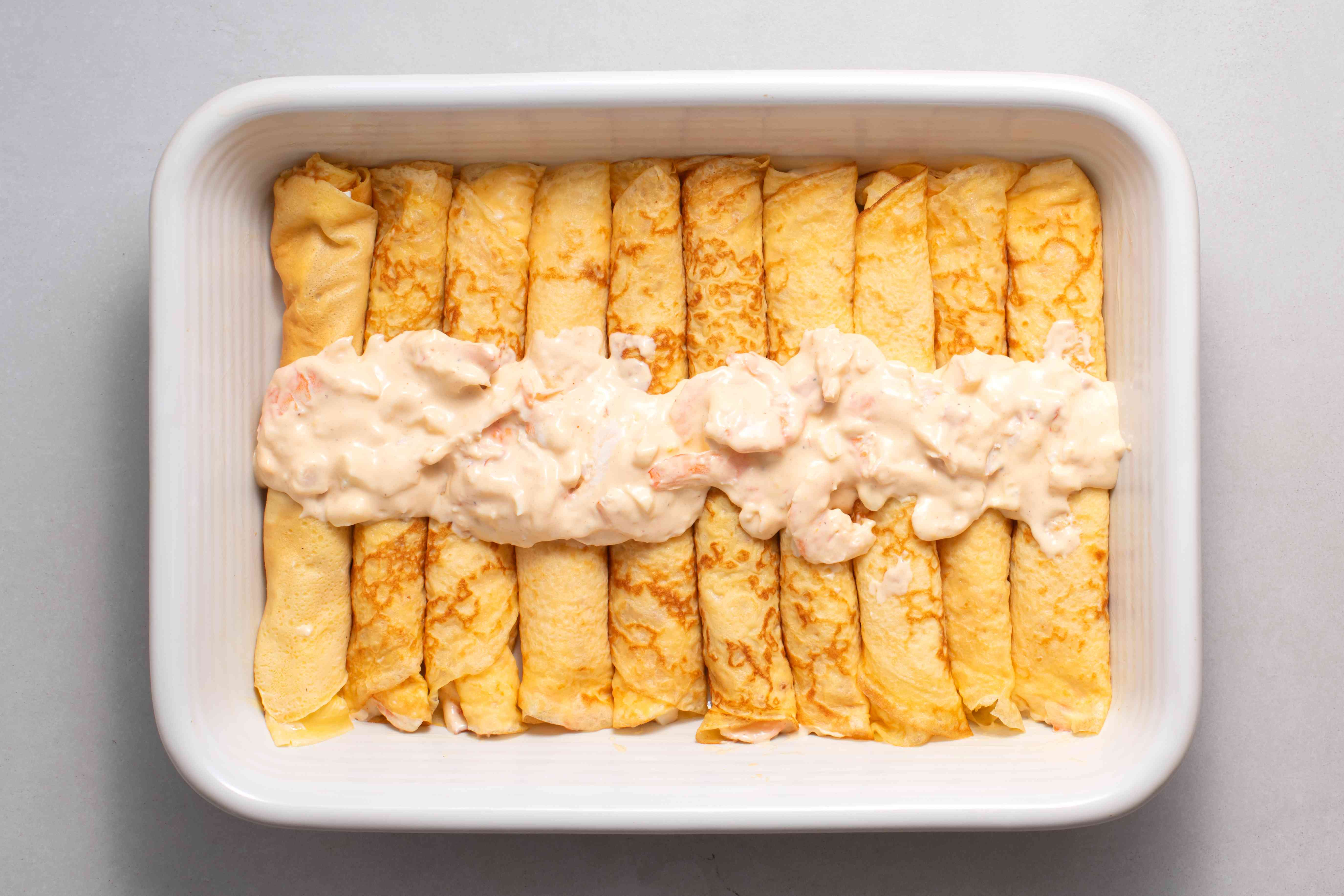 seafood crepes with seafood mixture on top in a baking dish