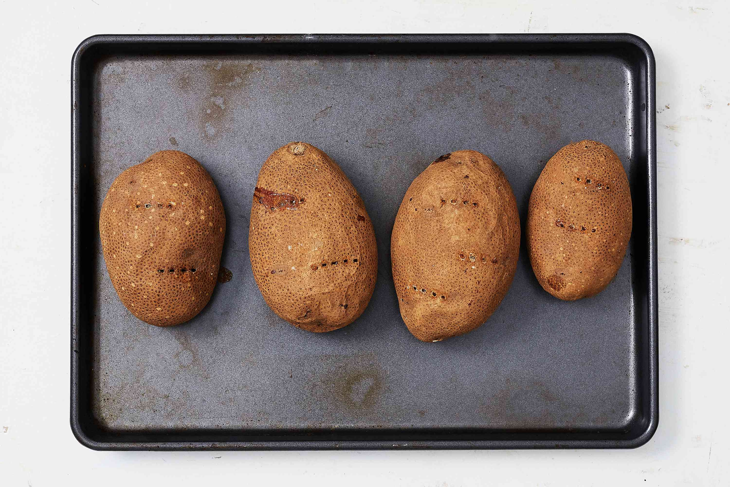 Prick potatoes in several places with a fork, on a baking sheet