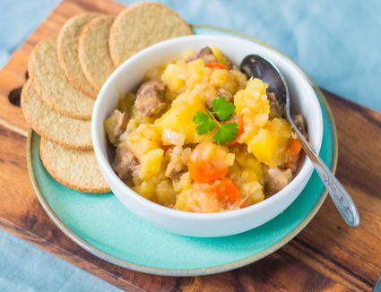 Traditional Scottish stovies recipe in a bowl with oatcakes served alongside