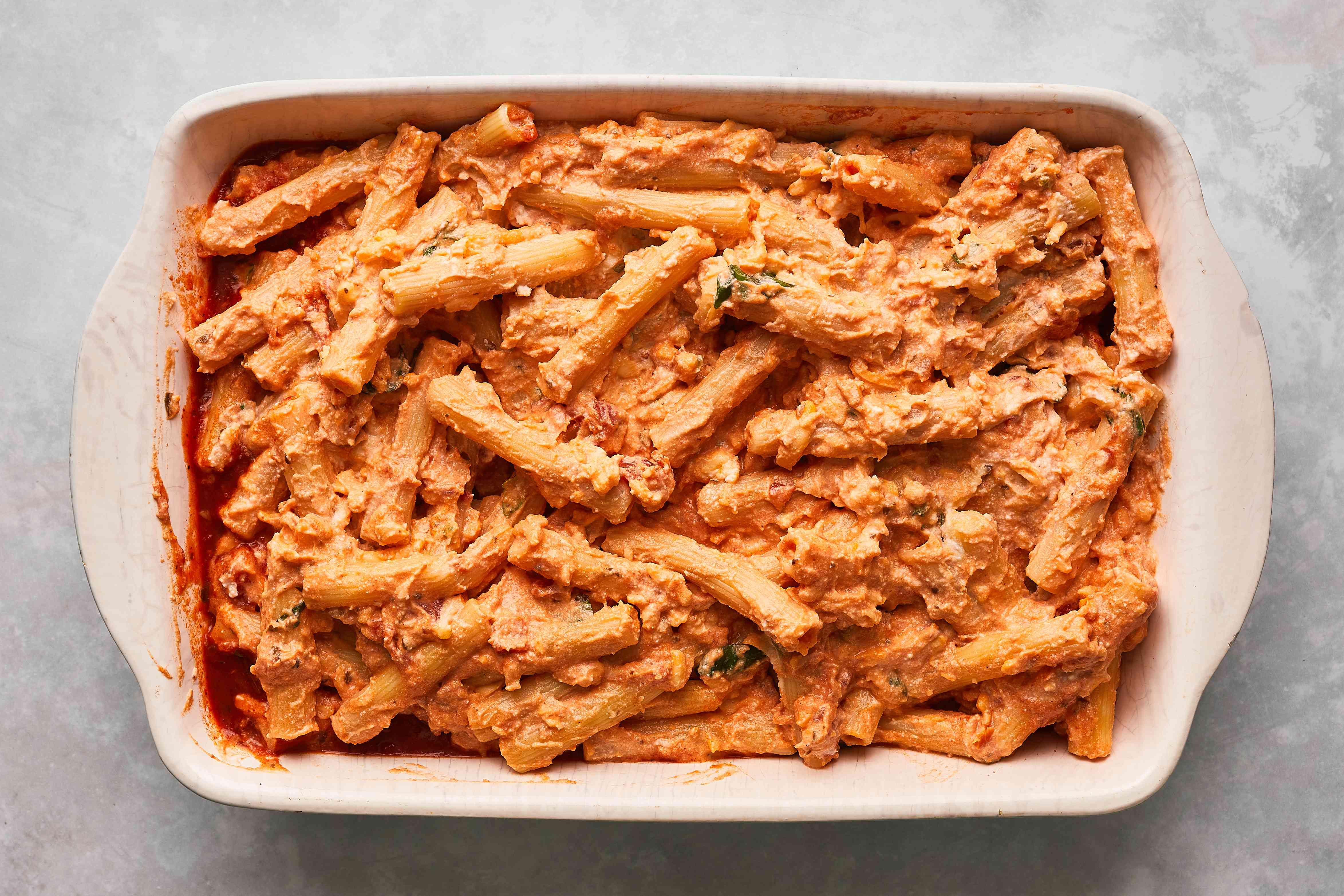 ziti with tomato sauce and cheese sauce in a baking pan