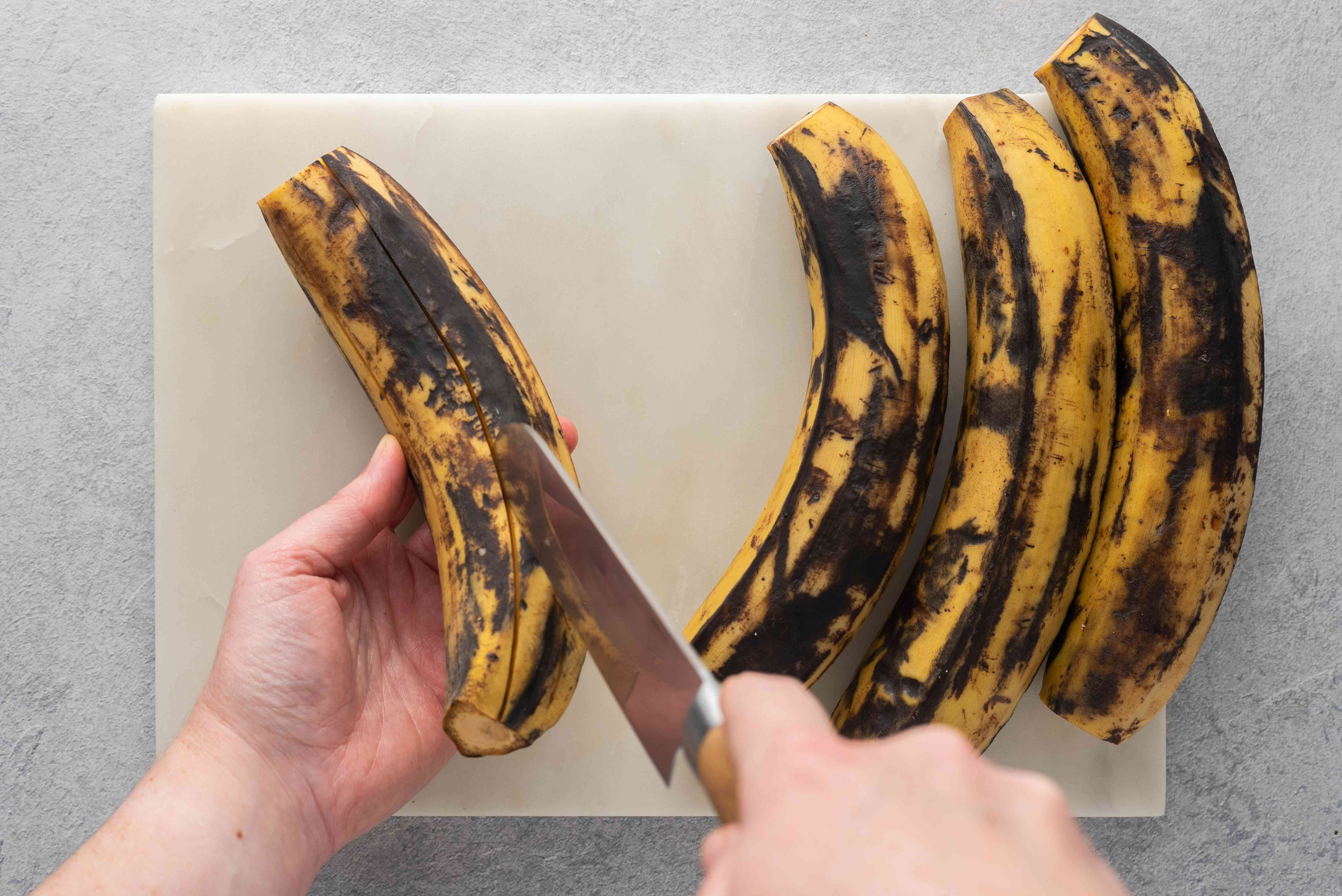 Score cuts through the skin down the length of the plantain