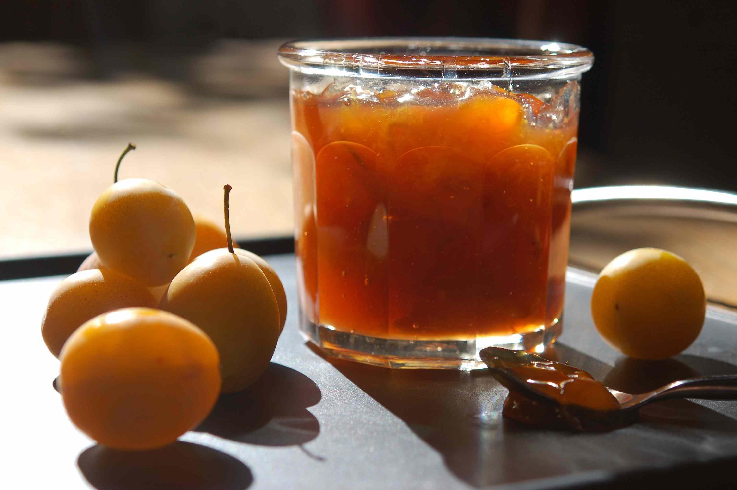 Fresh yellow plums and a jar of plum jam