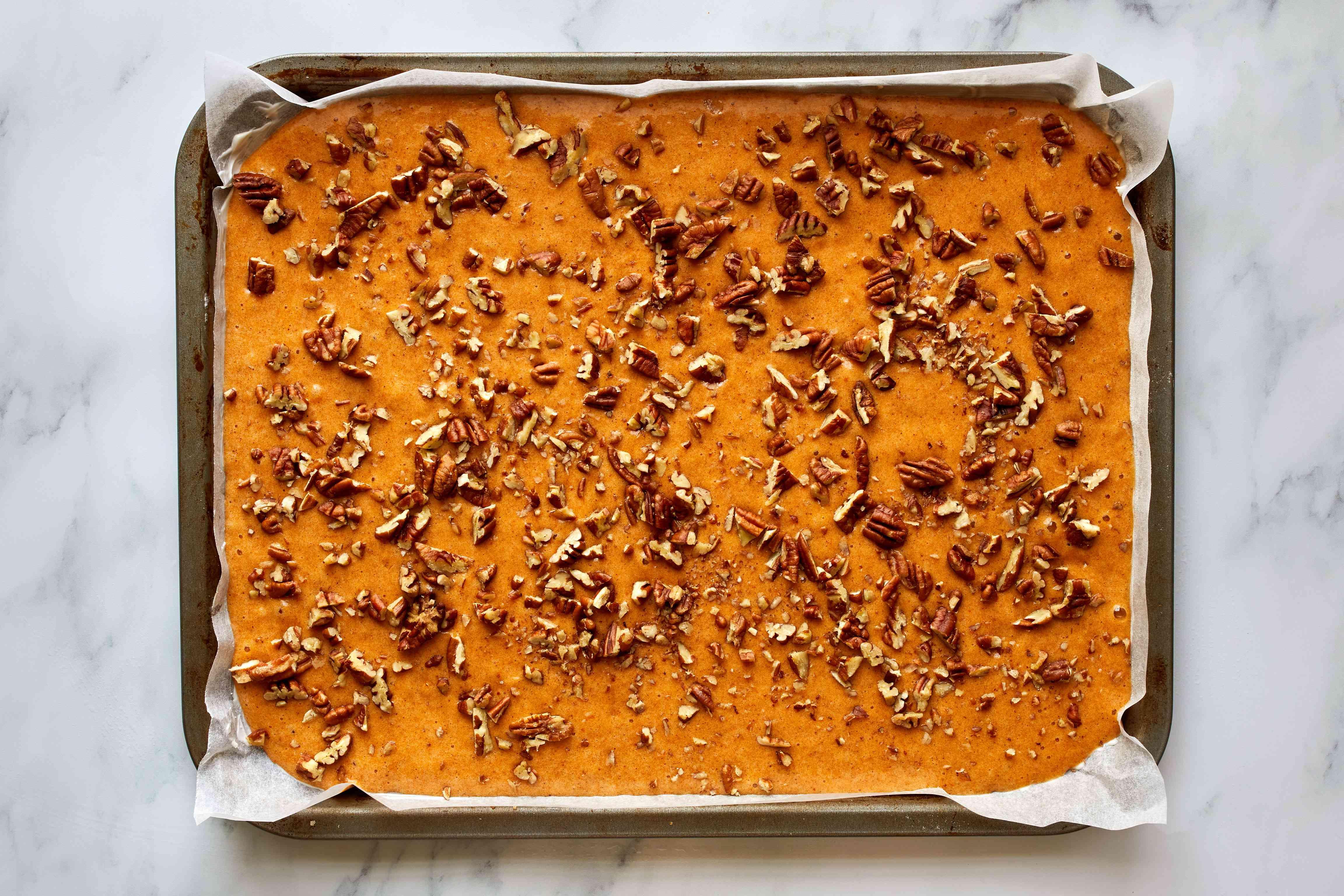 pumpkin cake batter on a baking sheet with pecans sprinkled on top