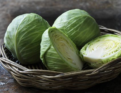 Halved and whole heads of green cabbage in a basket