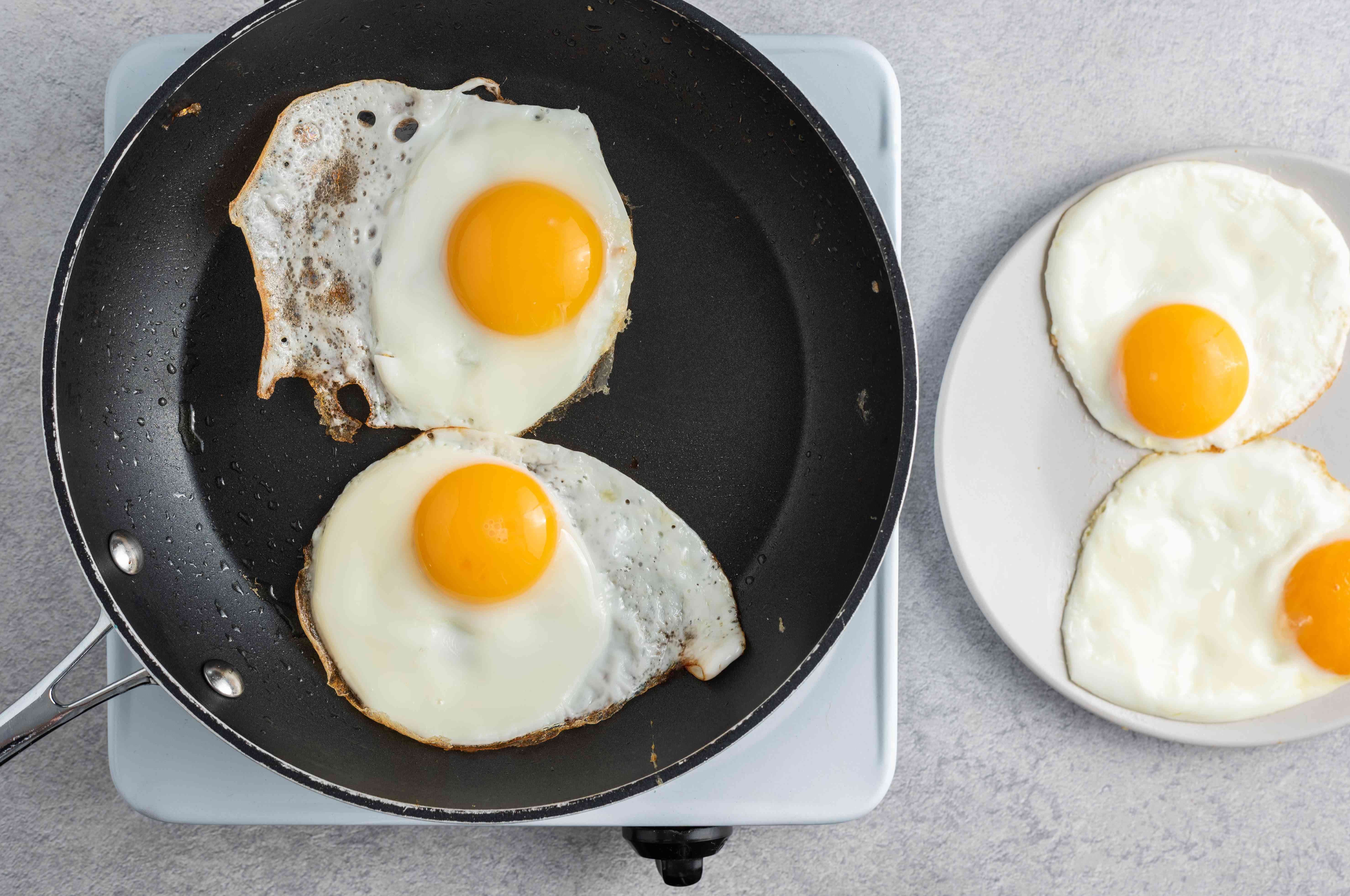 sunny side up eggs in a black non-stick pan