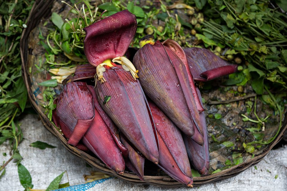 Dark red, edible banana blossoms in a pile