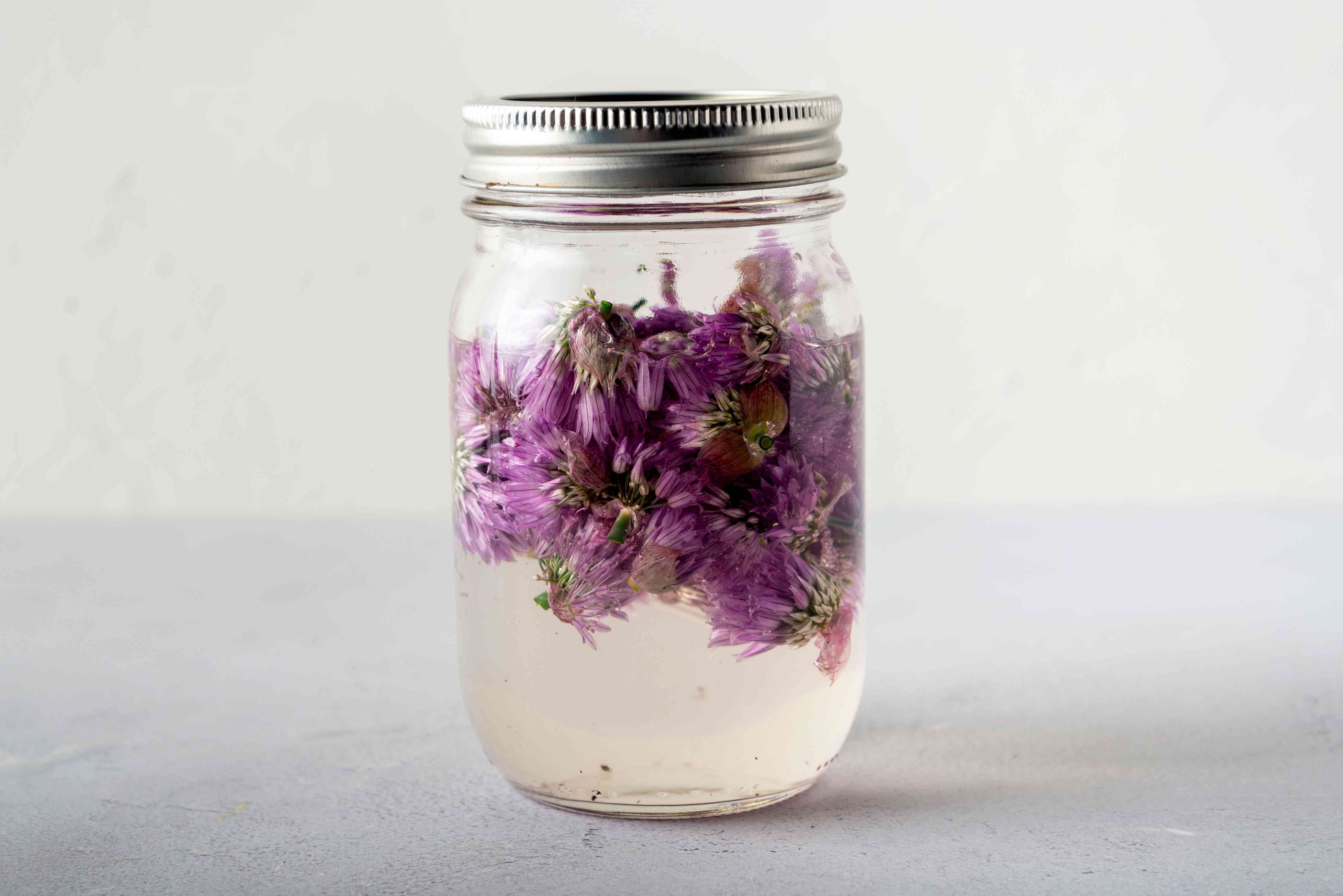 chive blossoms in vinegar in jar with lid on