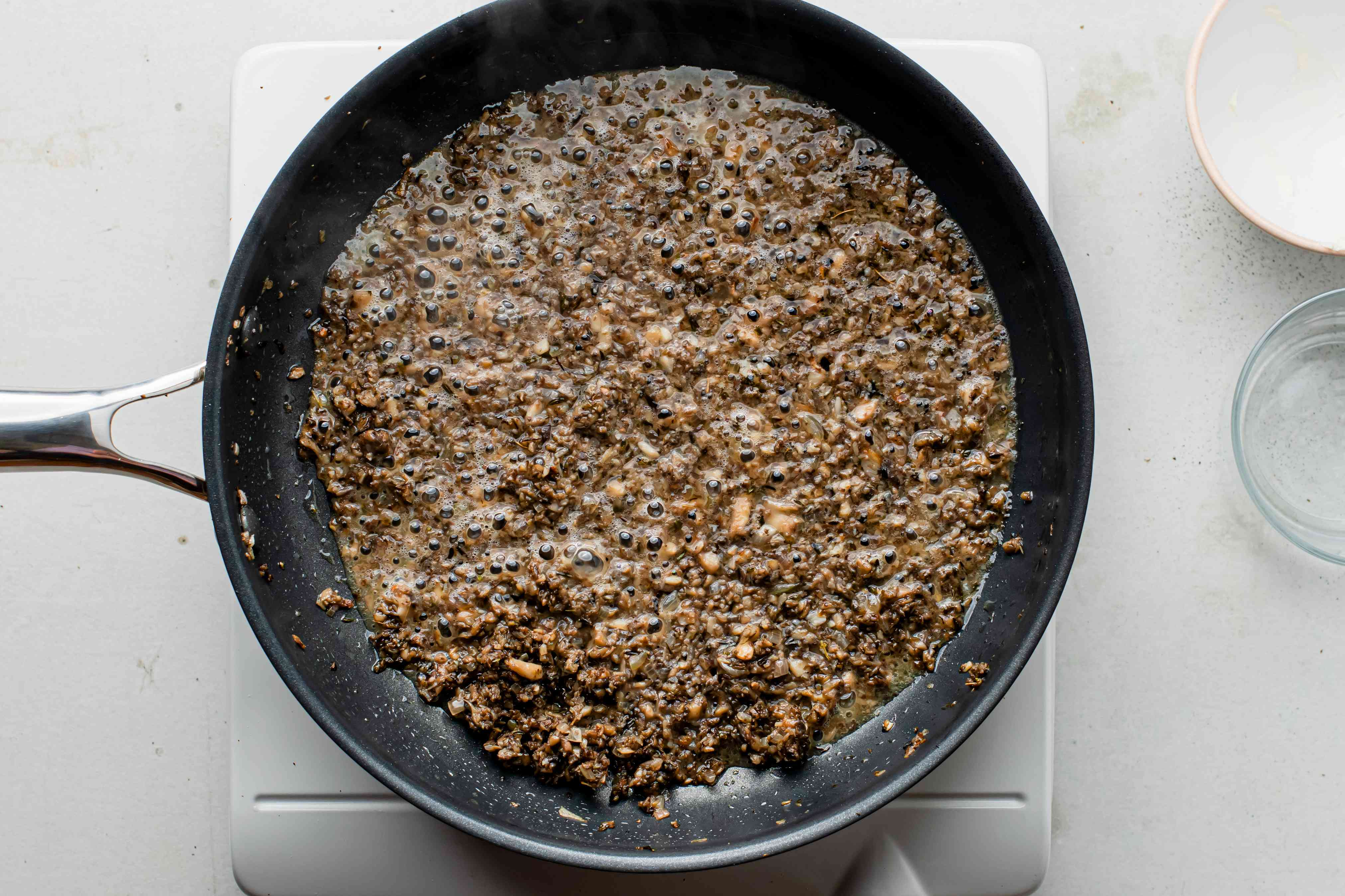 Mushroom mixture cooking in vermouth, in a black nonstick pan