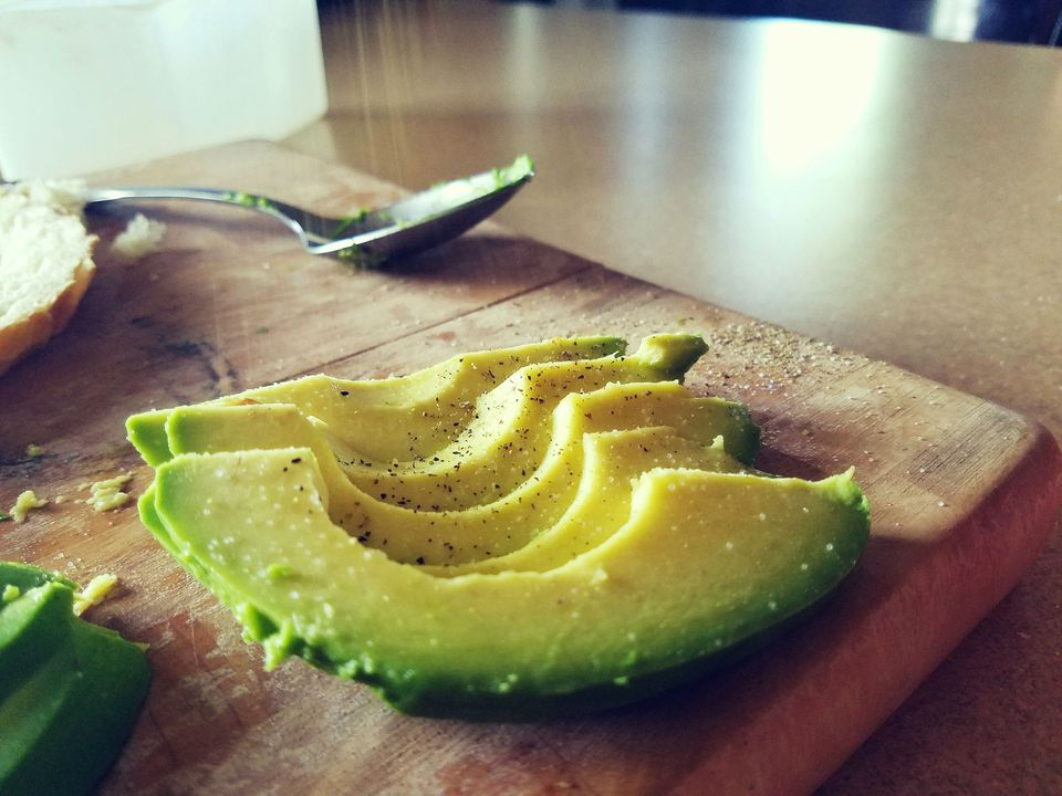 Slices of fresh avocado sprinkled with seasoning and resting on a cutting board