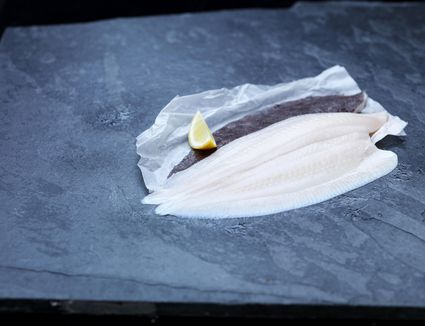 High angle view of raw lemon sole fillet and lemon wedge on baking paper and slate