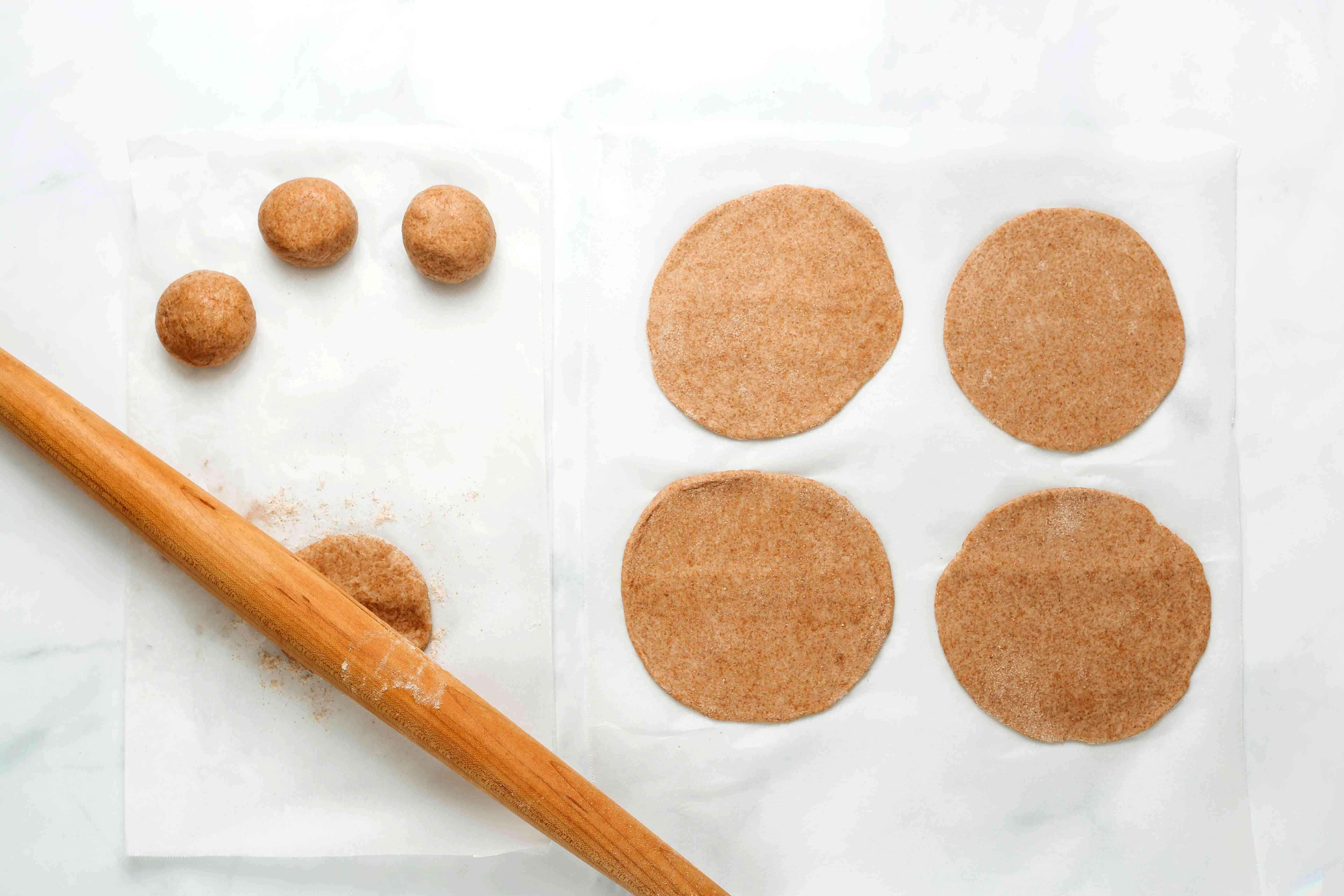 Wheat flour dough balls rolled out into round shapes on parchment paper
