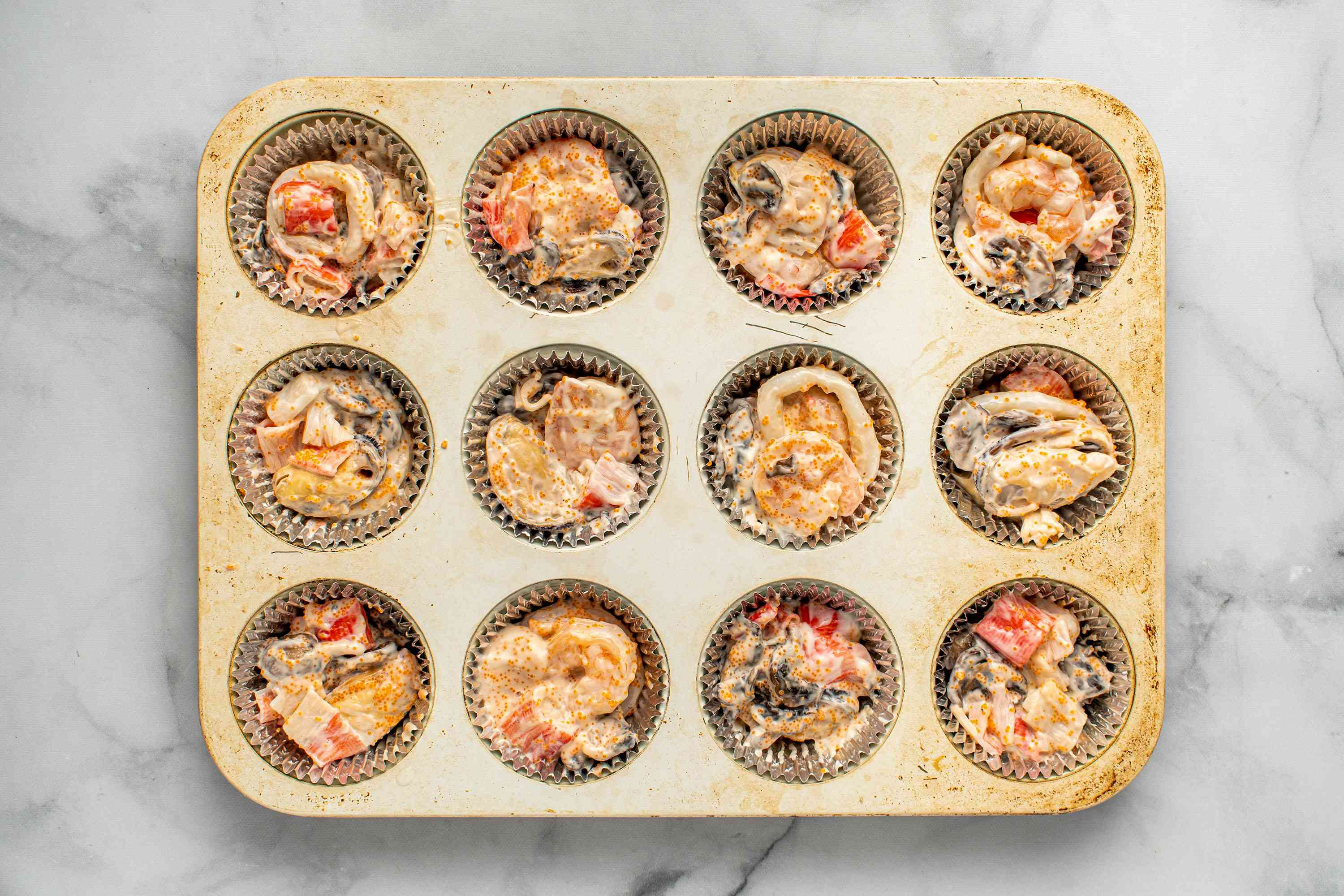 seafood, cooked mushrooms, mayonnaise and masago in a muffin tins