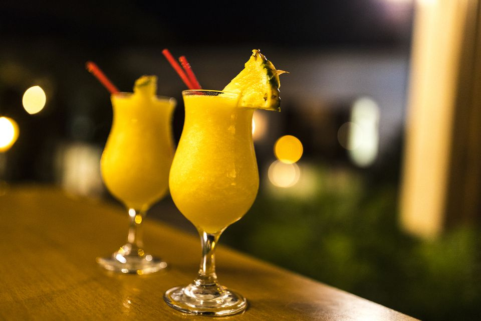 Two mango passion cocktails garnished with pineapple and set on a bar