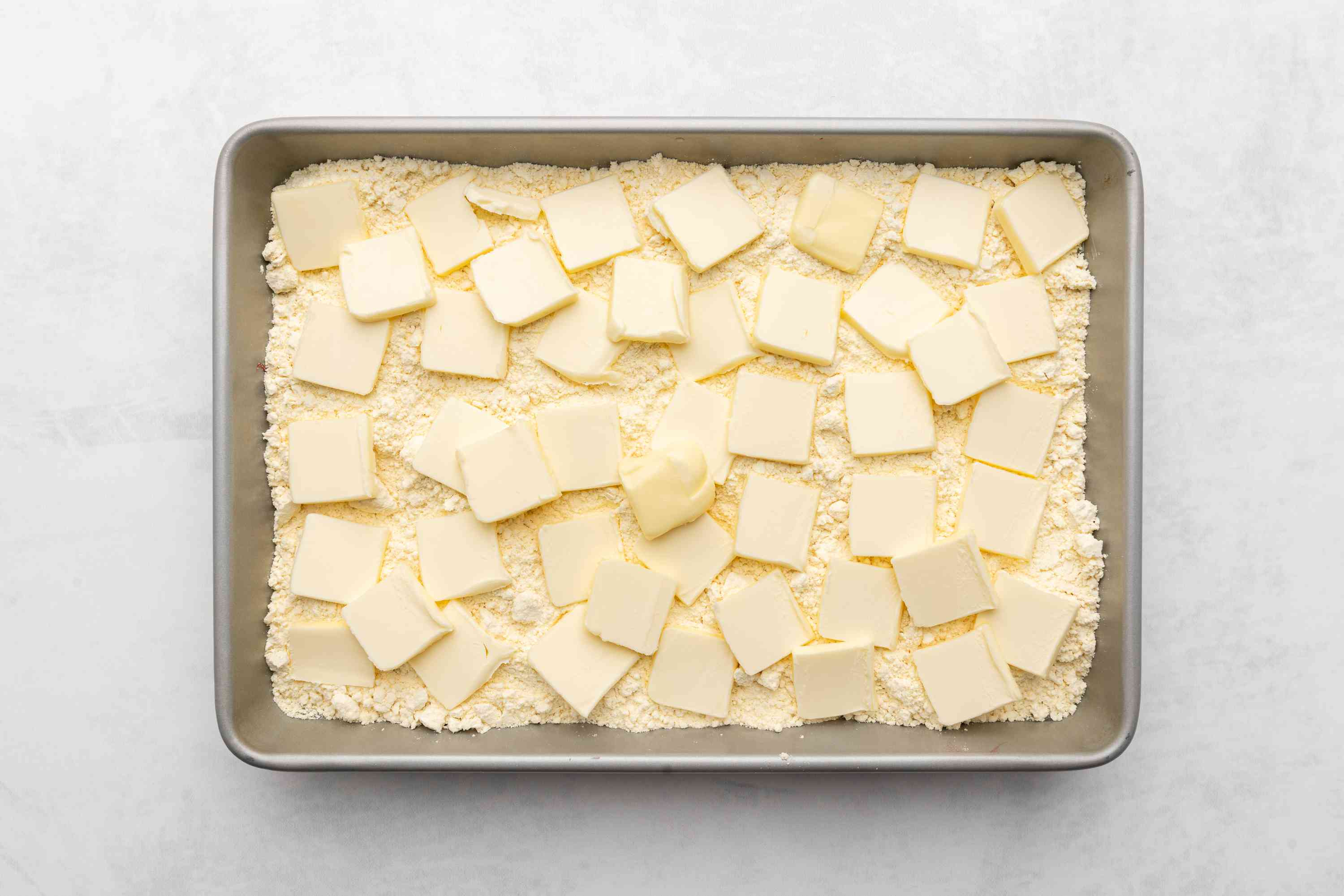 butter pieces of on top of the cake mix in a baking dish