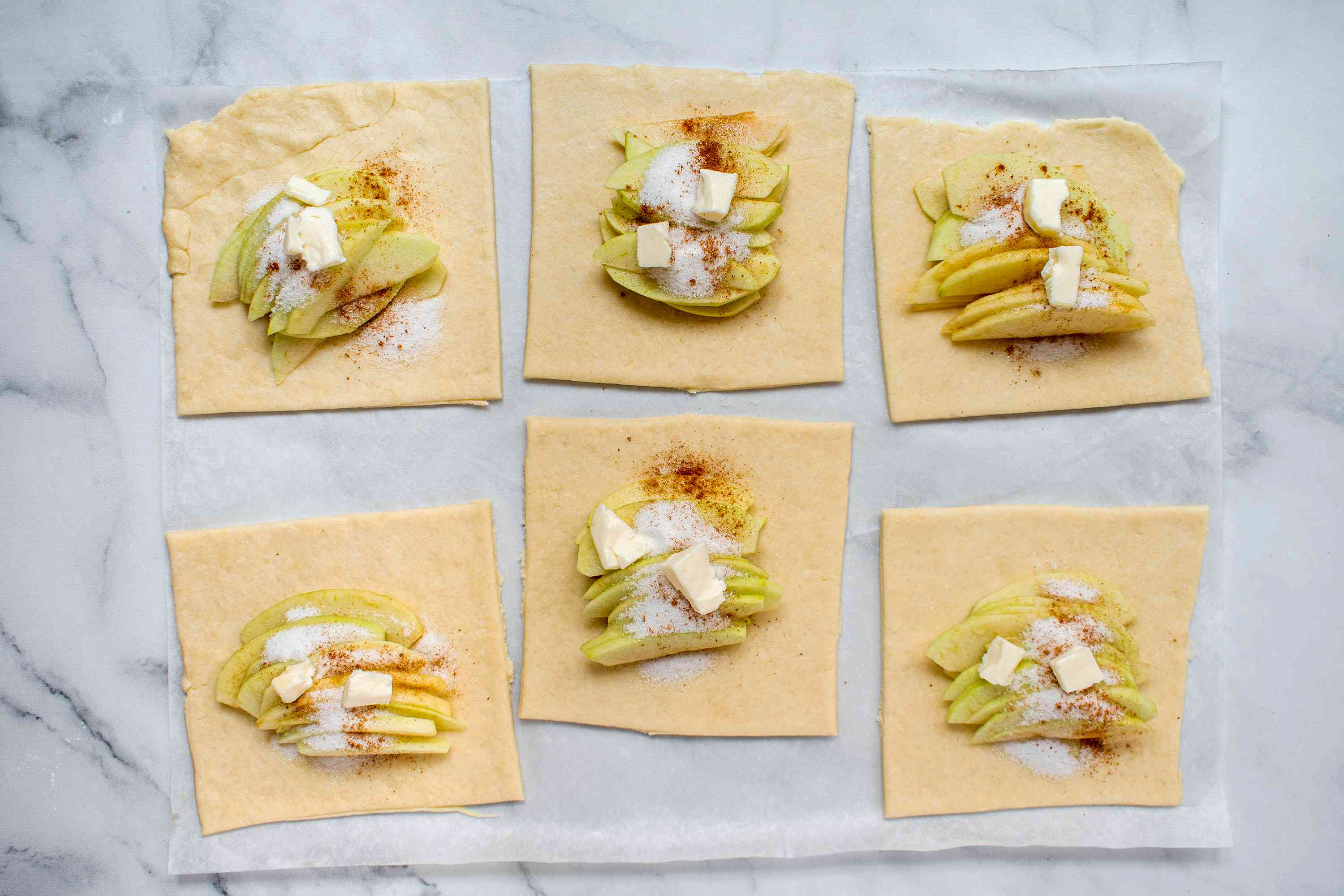 butter added on top of the apples, cinnamon and sugar on the dough squares