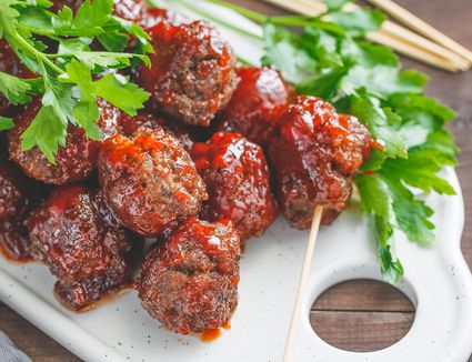 Grape jelly meatballs on a white plate with parsley