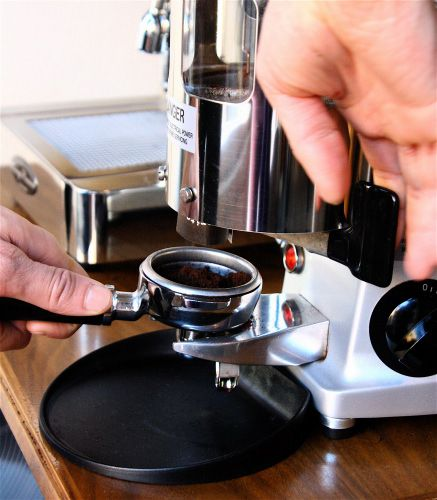 An image of espresso beans being ground in a coffee grinder.