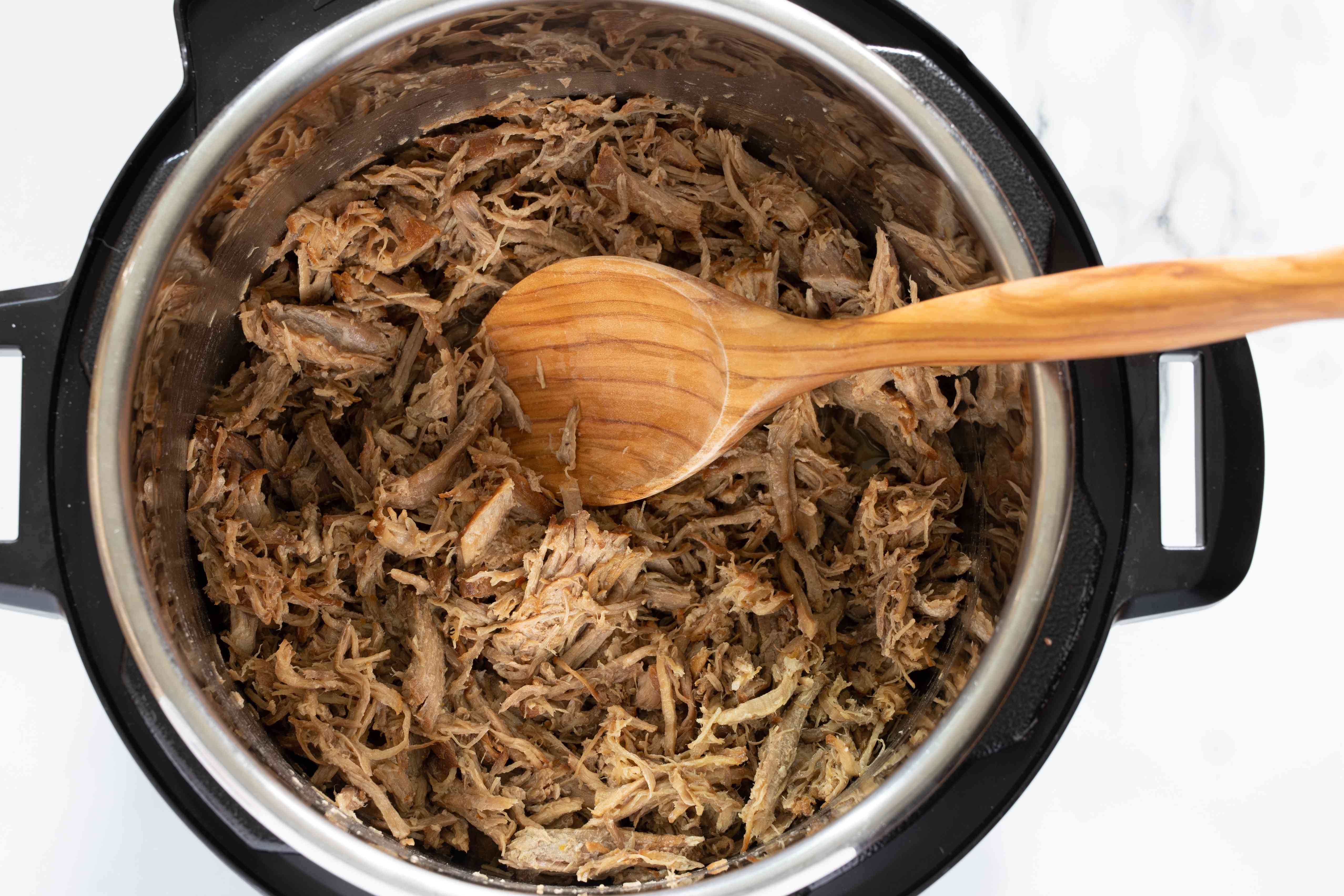 Heating the shredded pork and juices