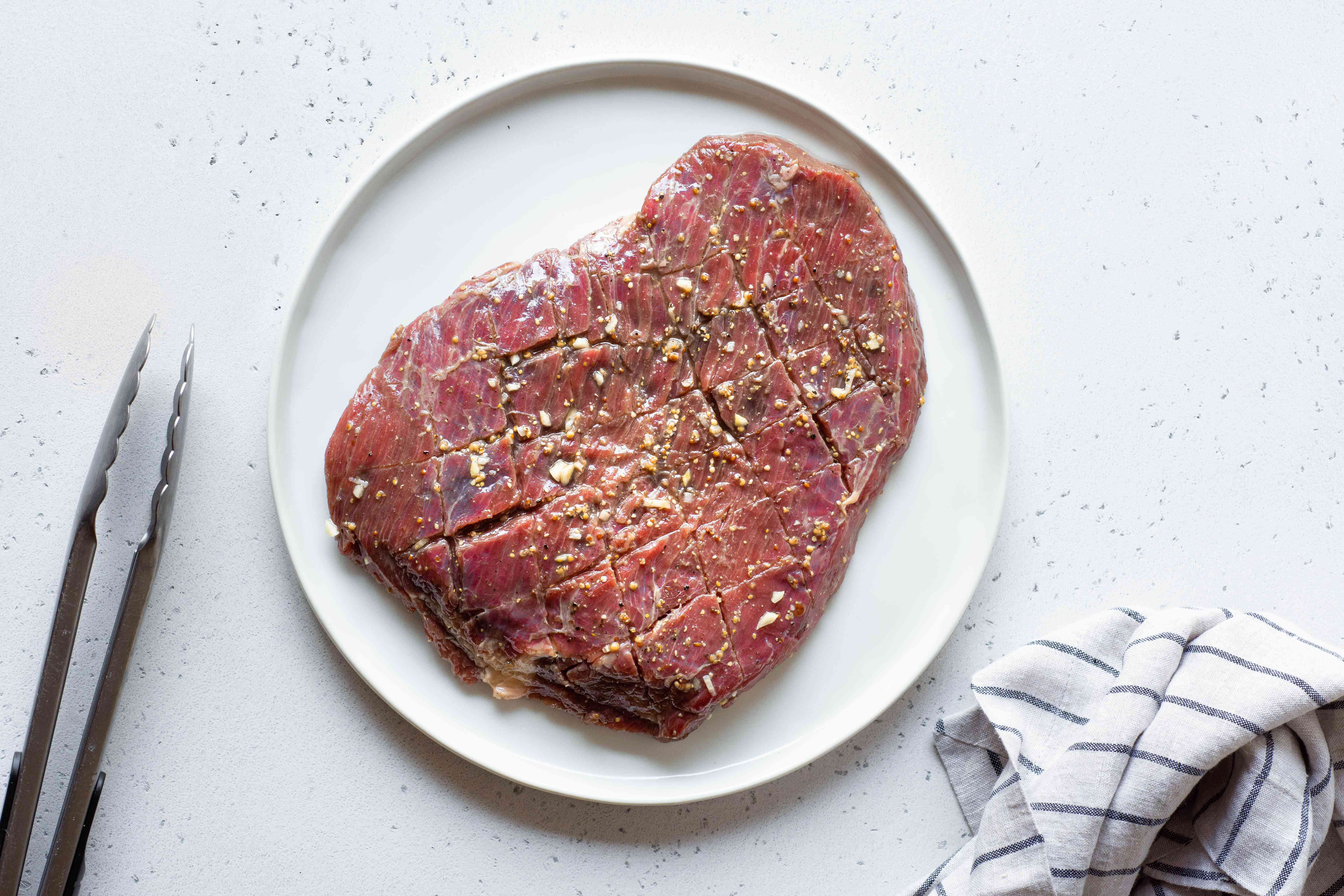 marinaded flank steak on a white plate