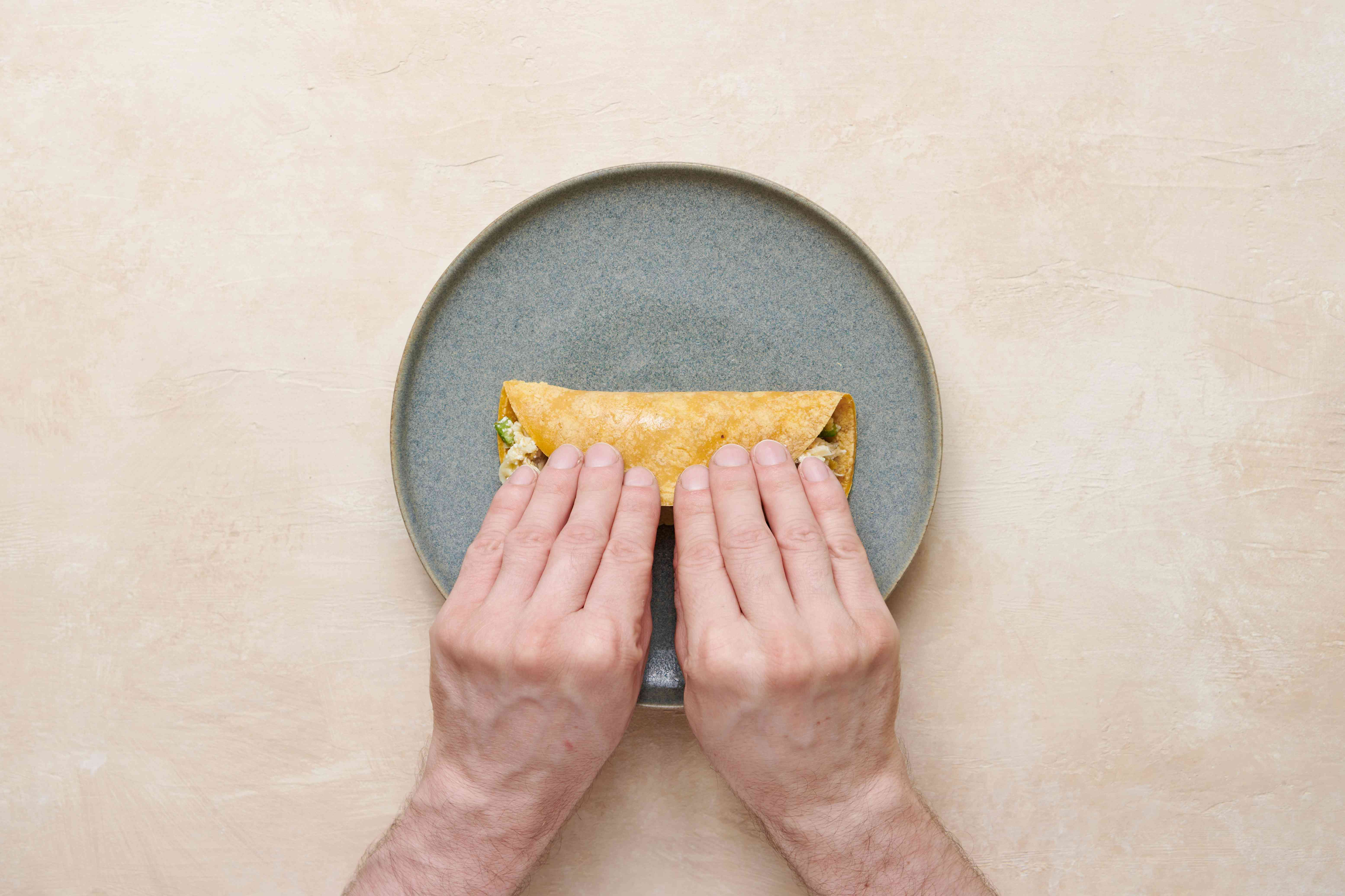 Folding the enchilada around the filling, on a plate