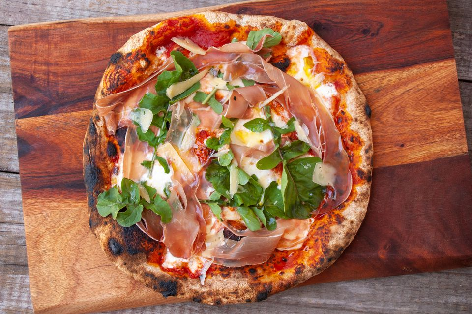 pizza with prosciutto, burrata, arugula and parmesan