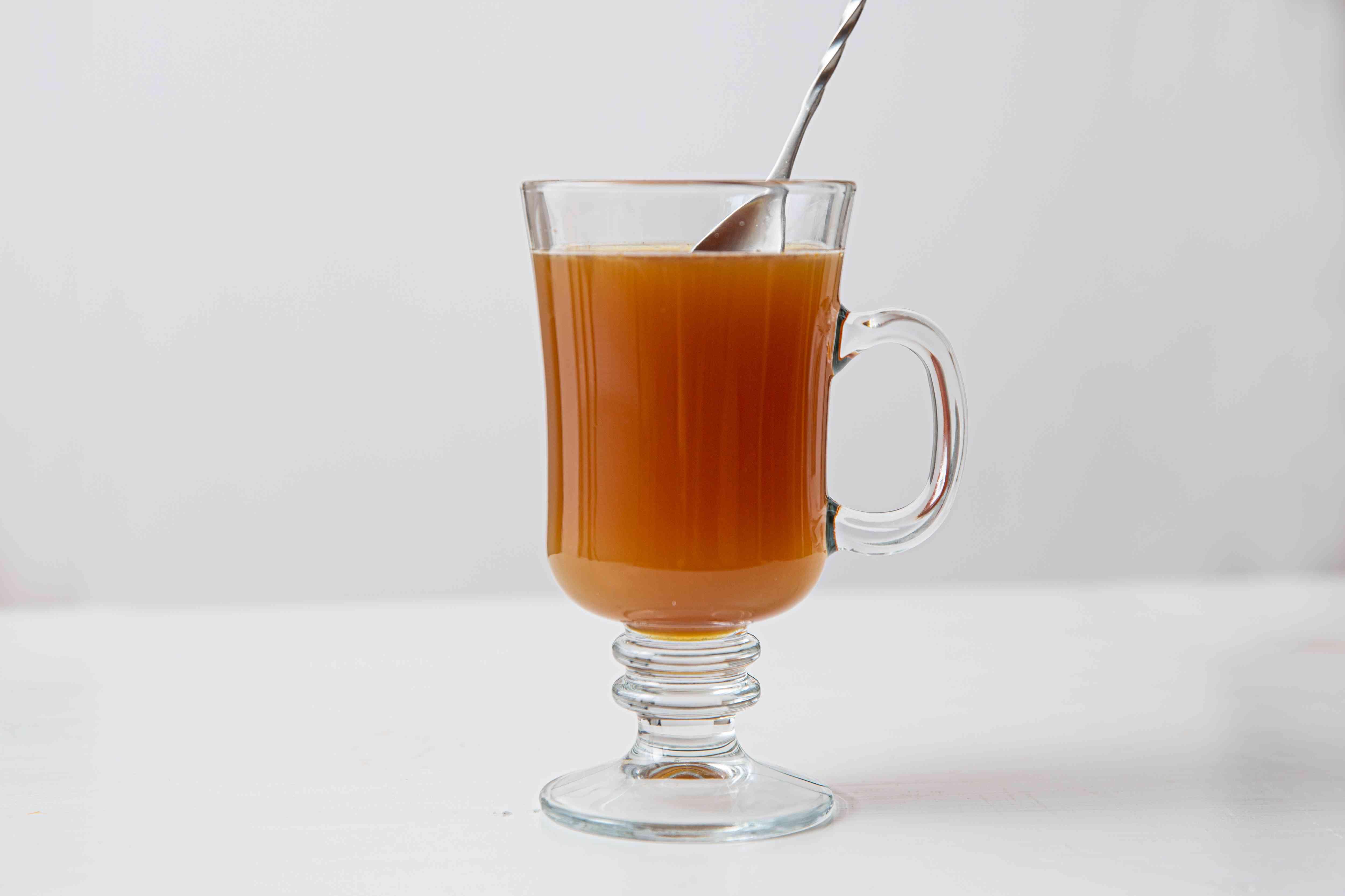 Whiskey with honey and apple cider in an Irish coffee glass