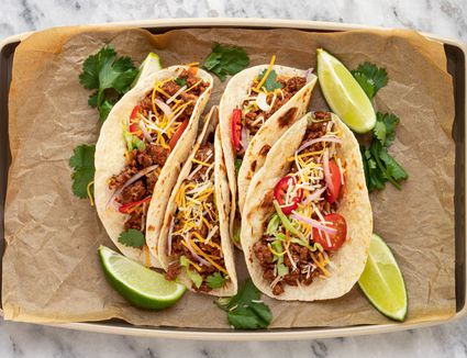 tacos with ground beef, tomatoes, lime wedges, and cilantro