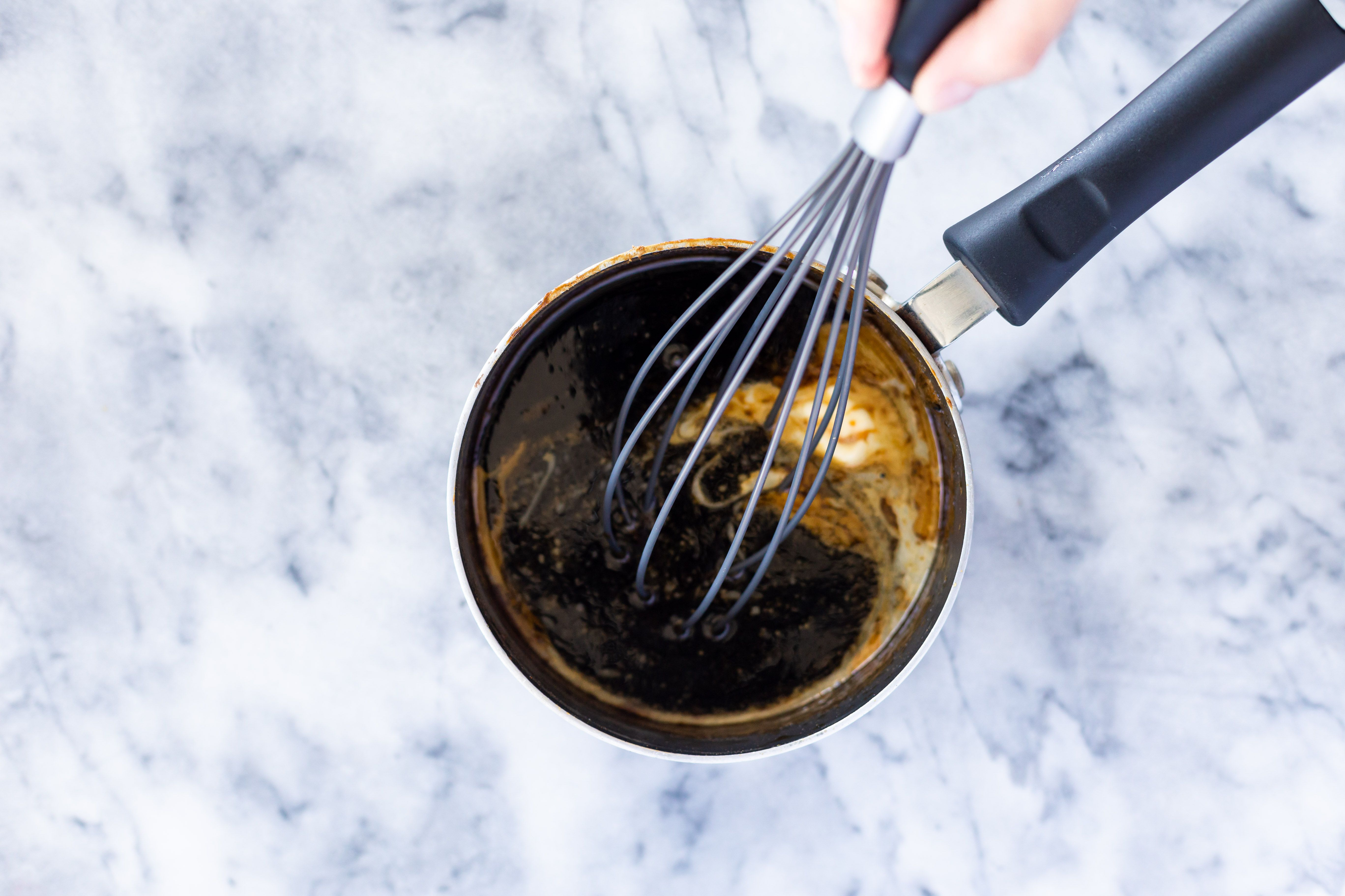 Whisking butter and maple syrup into sugar mixture