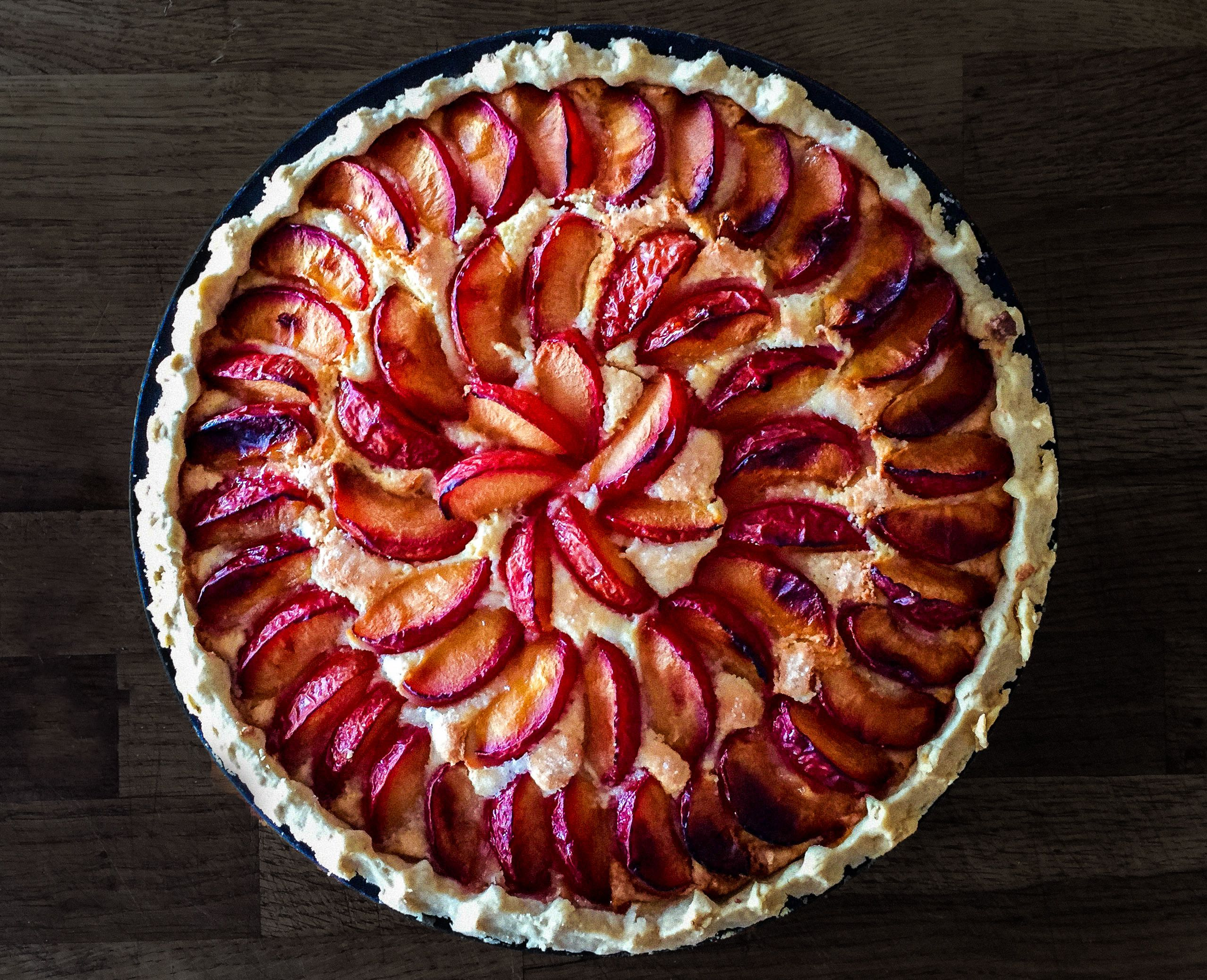 A plum and almond tart topped with sliced plums