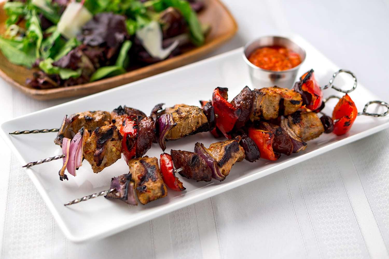 Pork kebabs skewers with sauce and salad