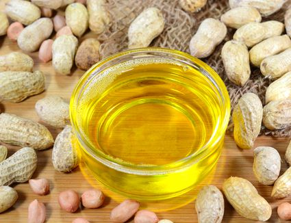 Small bowl of peanut oil surrounded by peanuts.