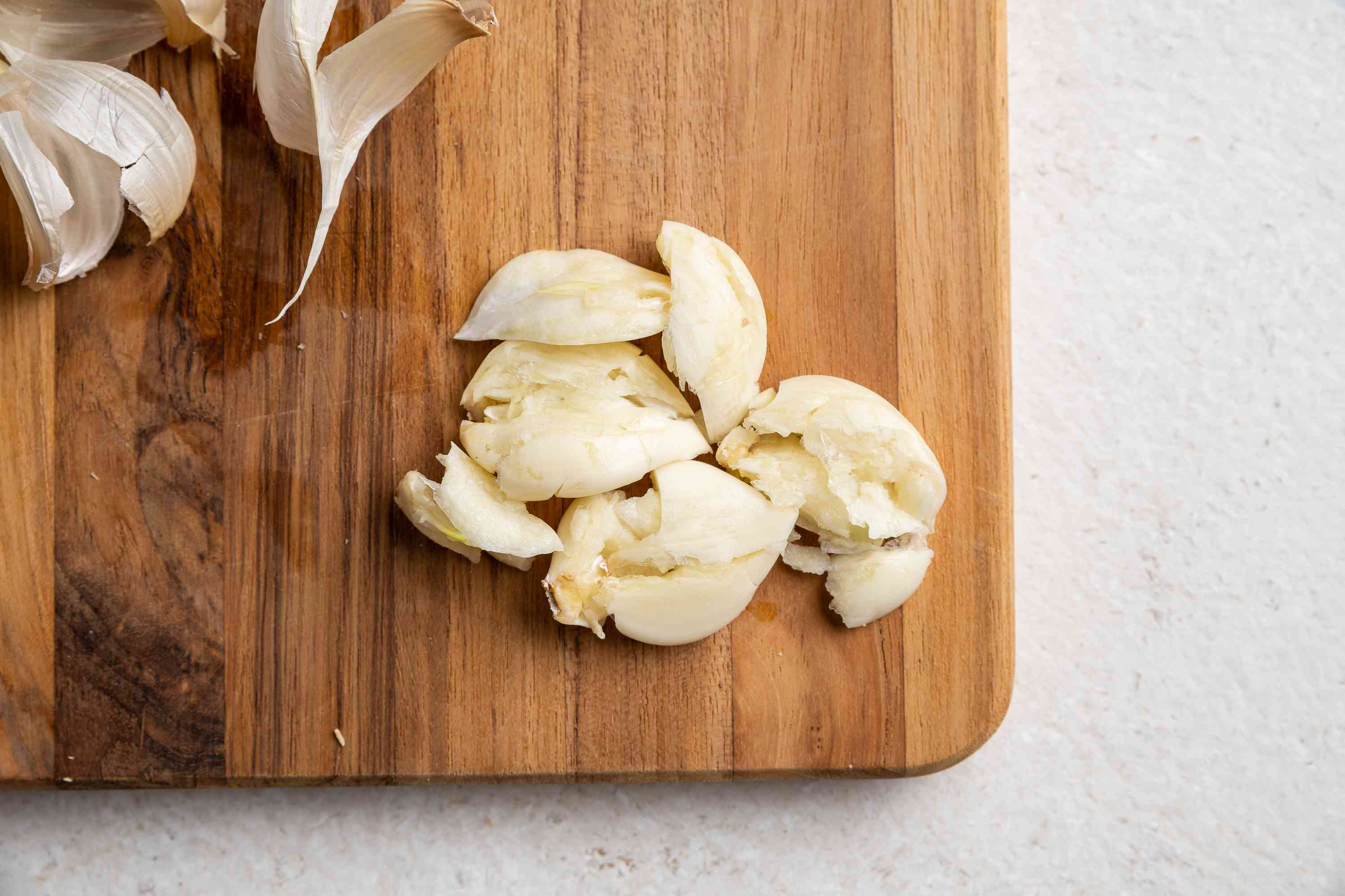 Smash the garlic cloves and discard the skins