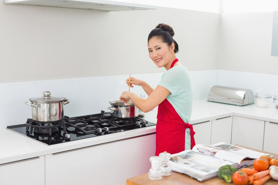 woman cooking using a cookbook