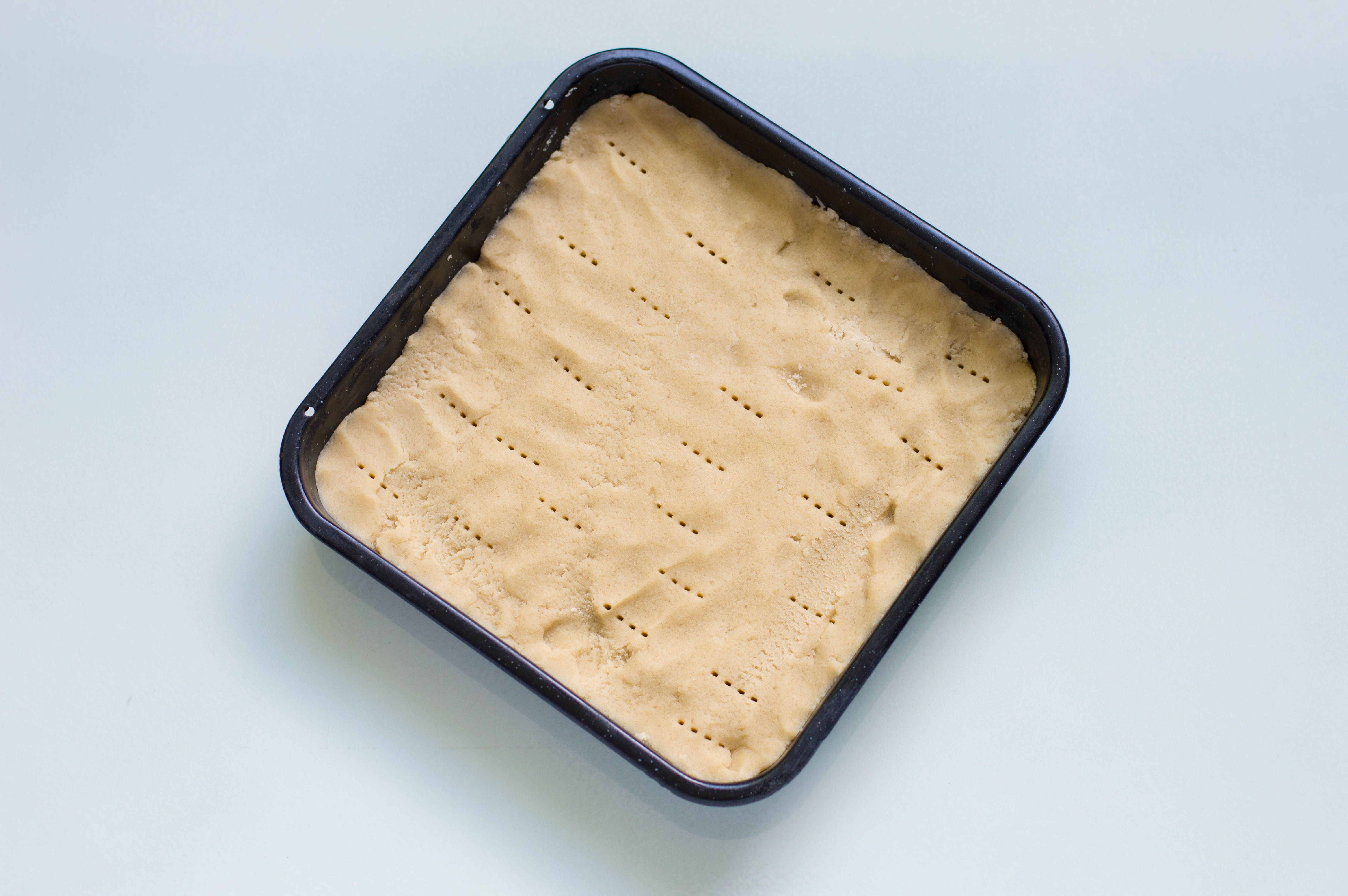 Unbaked shortbread dough in a square pan
