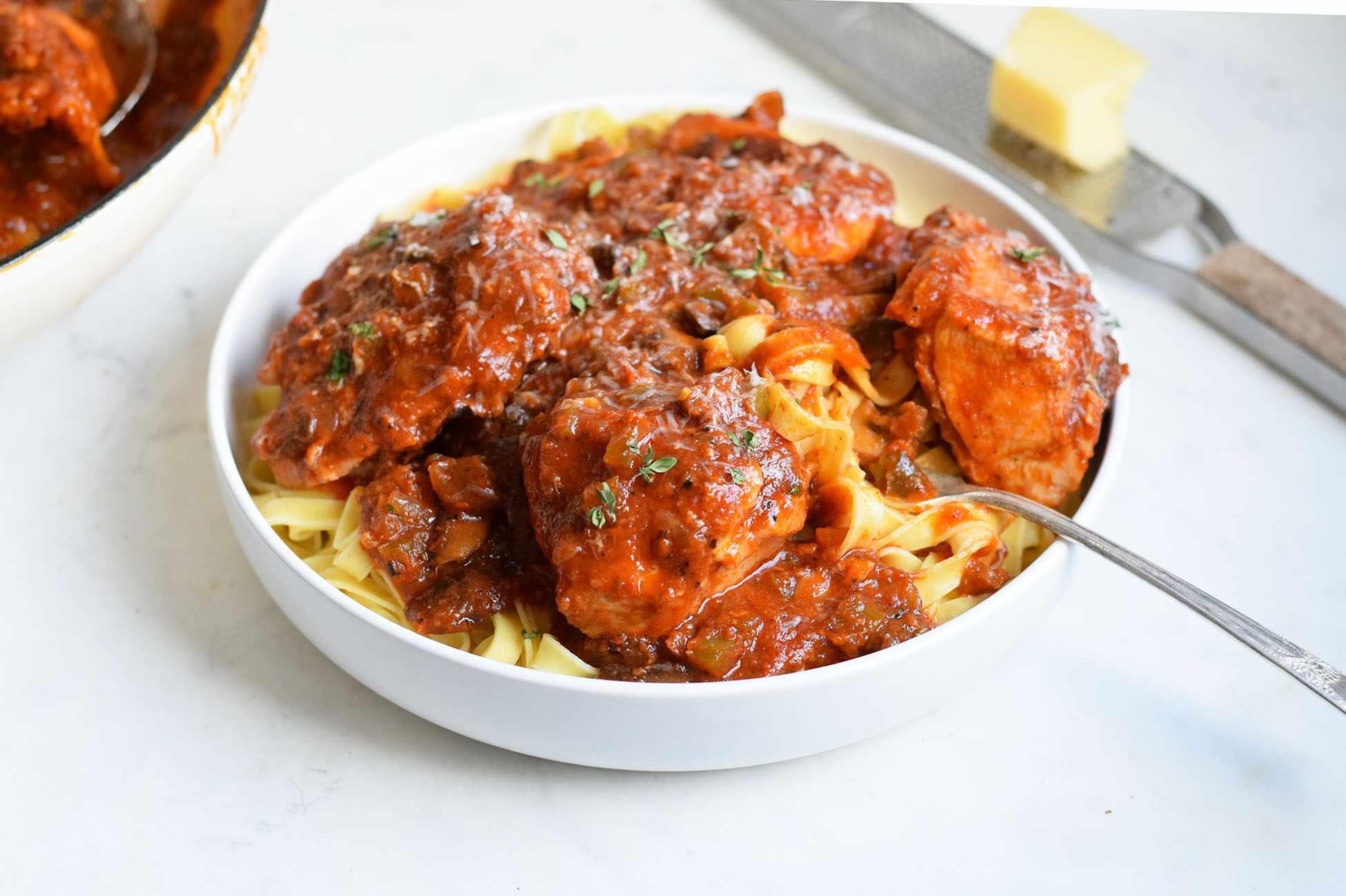 Chicken cacciatore in a bowl over pasta