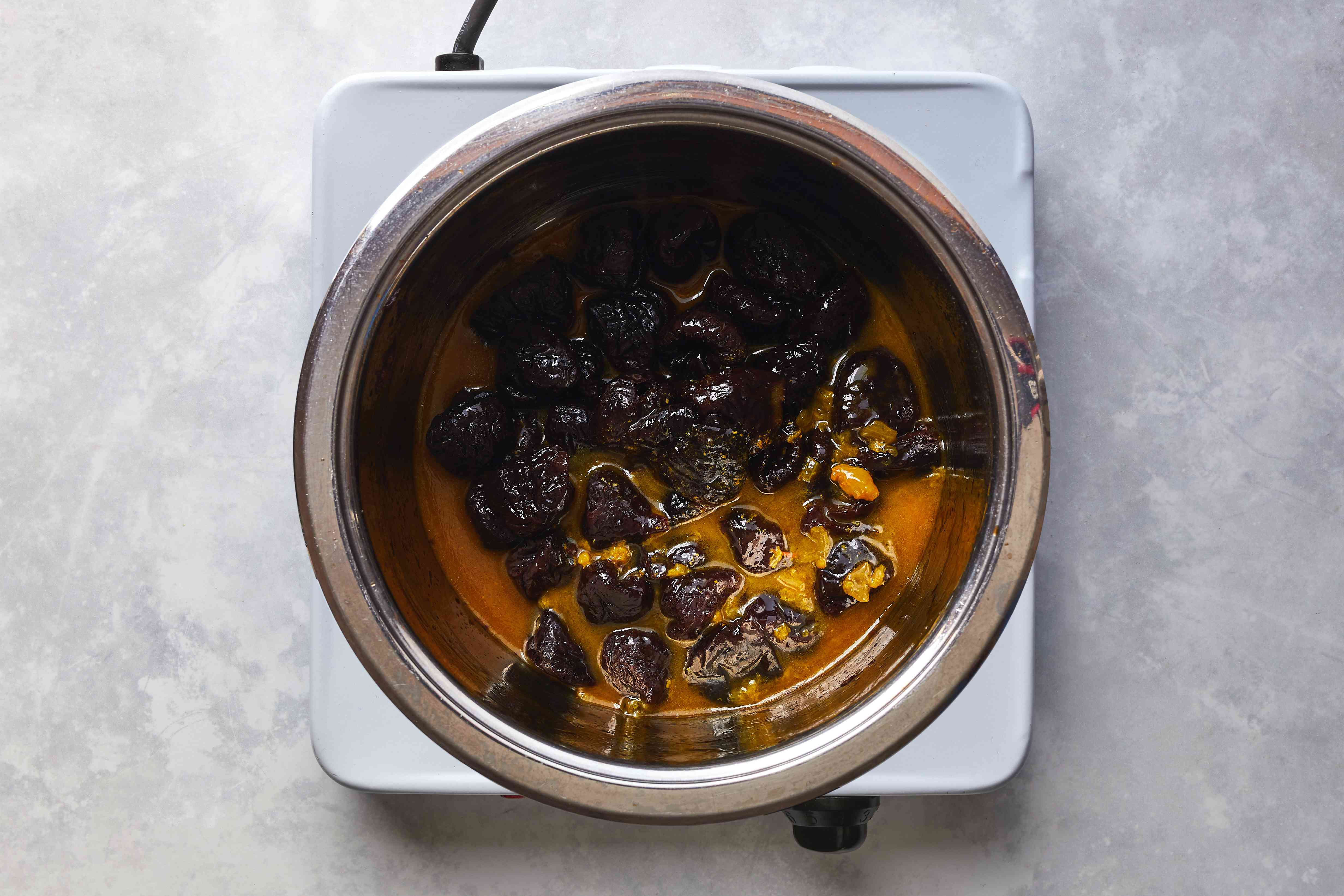 prunes with lamb cooking liquid in a pot